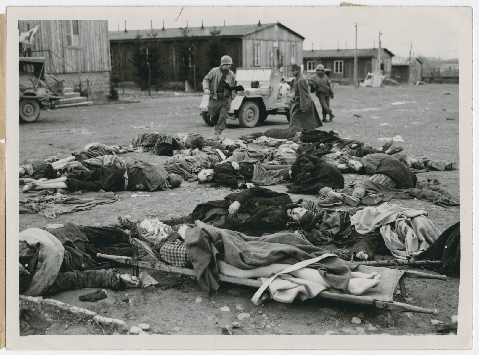 "The U.S. Army inspects bodies of slain prisoners at the Ohrdruf concentration camp.  Original caption reads:  ""Here are the bodies of some of the slain prisoners.  The case of the man on the litter in the foreground is being carefully investigated.  According to survivors, this man always said he was an American, and he is believed to have been either a flyer or a paratrooper""."