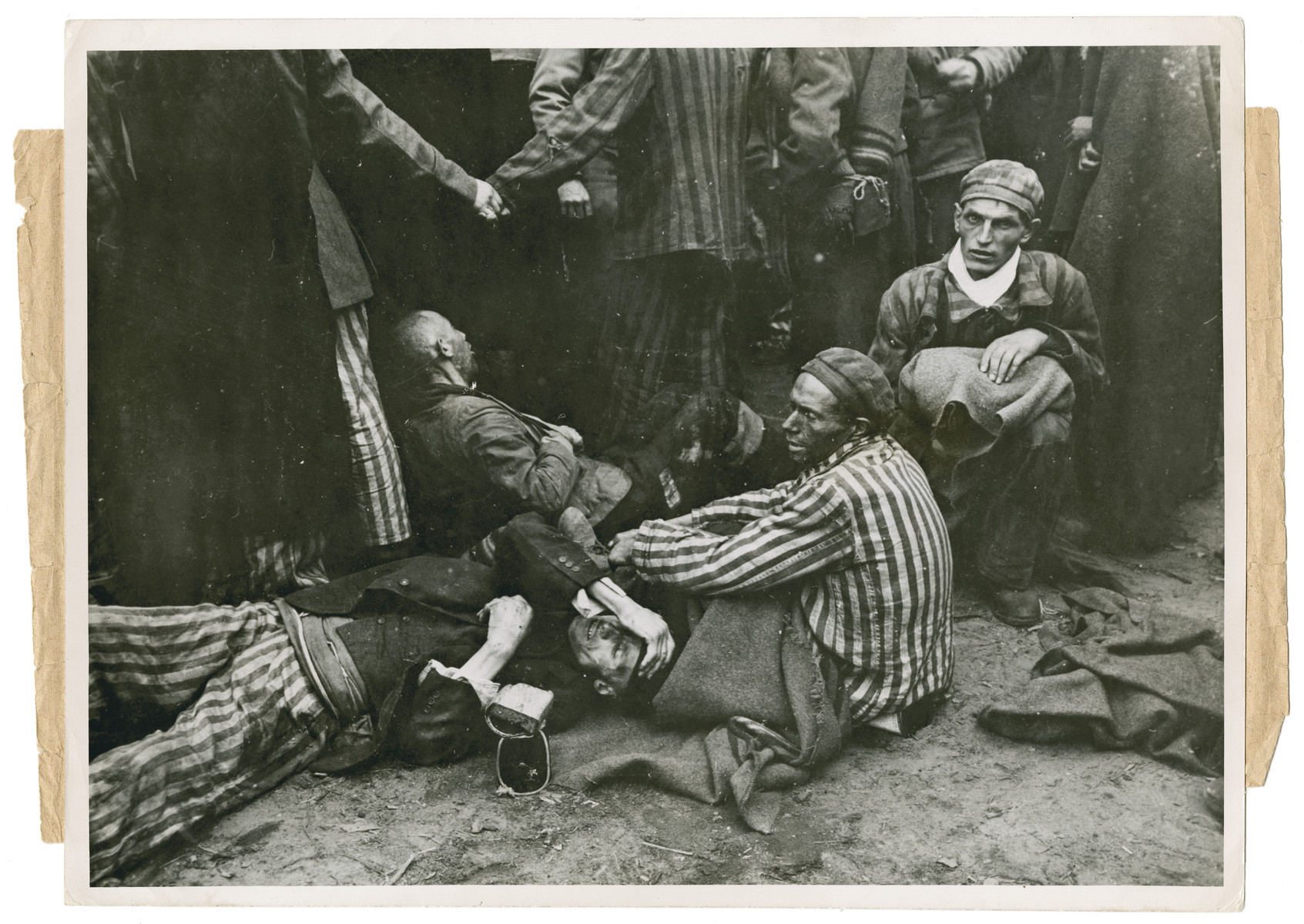 "Original caption reads:  ""Tortured, half-starved prisoners anxiously await transportation from the Wobbelin camp to a hospital shortly after liberation""."