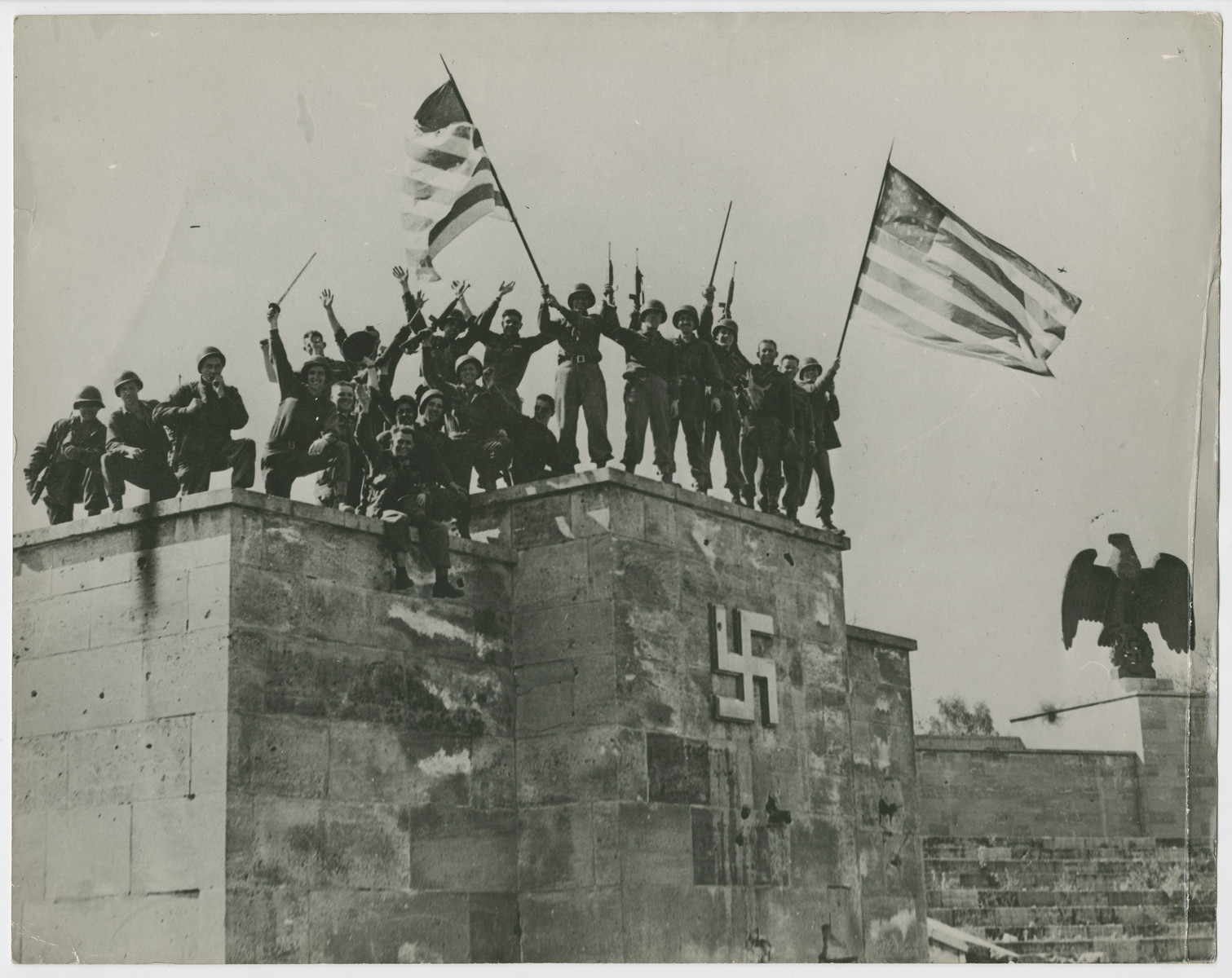 """Troops of the 45th Division, Seventh U.S. Army wave American flags in the Nuremberg stadium.  Original caption reads:  """"U.S. Soldiers Capture Nuremberg.  Troops of the 45th Division, Seventh U.S. Army, wave battle-worn American Flags from the dais of the Luitpold Arena in Nuremberg, Germany, after capture of the shrine city of the Nazi Party April 20, 1945.  This is the very spot from which Hitler, Goering, Gobbels and Hiimmler harangued their massive Nazi audiences at party festivals in the defiant prewar days.  After the U.S. forces had crushed the last flicker of enemy resistence in the city, masses of liberated foreign slave workers streamed into the huge stadium""""."""