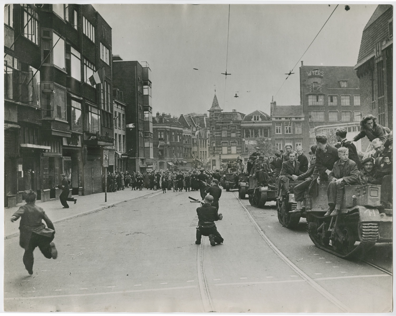 """Sharpshooters aim at German snipers who fired at a Dutch victory parade in Utrecht.    Original caption reads:  """"Crowds celebrating victory in the streets of Utrecht, Holland, are fired on by Nazi fanatics hiding in a building overlooking the parade.  After a sharp skirmish, the Germans were captured by Dutch patriots and the celebration was resumed.  Here, as the Nazis open fire on the victory crowds, Dutch patriots go into action""""."""
