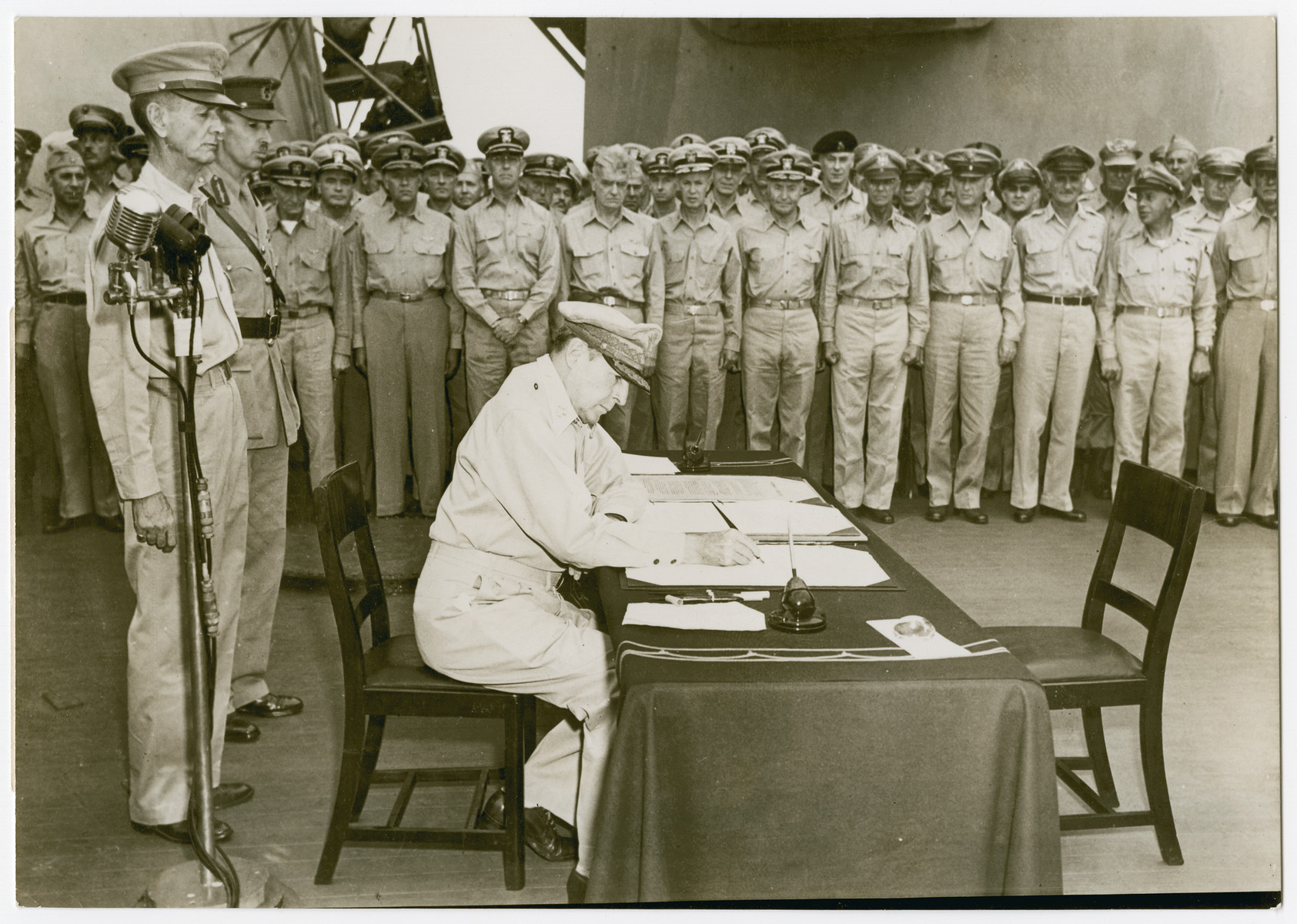 """U.S. General of the Army, Douglas MacArthur, signs the Japanese surrender document aboard the U.S.S. Missouri.   Original caption reads:  """"U.S. General of the Army, Douglas MacArthur, Supreme Allied Commander, signs the Japanese surrender document Sept. 1, 1945 aboard the U.S.S. Missouri.  Behind General MacArthur are U.S. Lieutenant General Jonathan Wainwright, hero of Bataan and Correaidor who was found in a Japanese prisoner of war camp Aug. 20, 1945, and British Lieutenant General Arthur E. Percival, who was forced to surrender Singapore to the Japense.  Both were liberated from the Japanese prison camp at Sian, Manchuria, by U.S. paratroops and Soviet forces.  Both were flown to Tokyo at General MacArthur's invitation to witness the surrender ceremonies""""."""