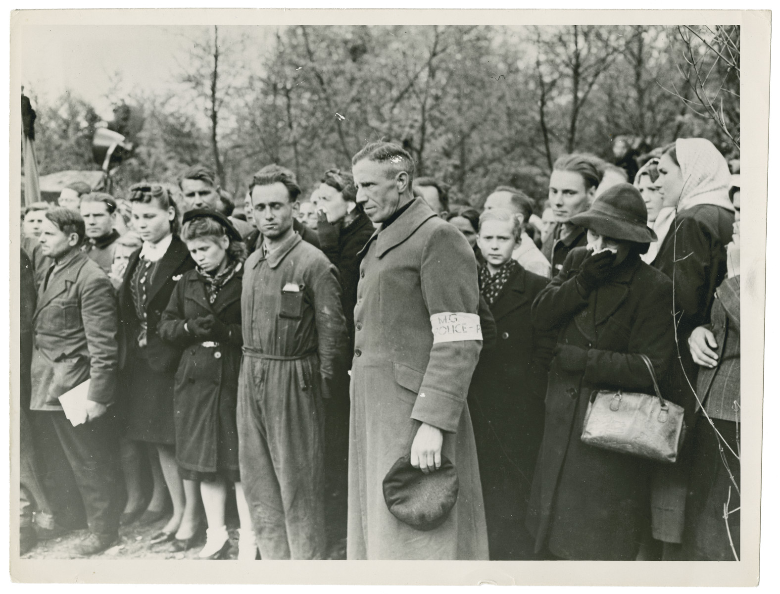 "Original caption reads: ""German civilians of Wuelfel watch the disinternment of the murdered Russian prisoners."""