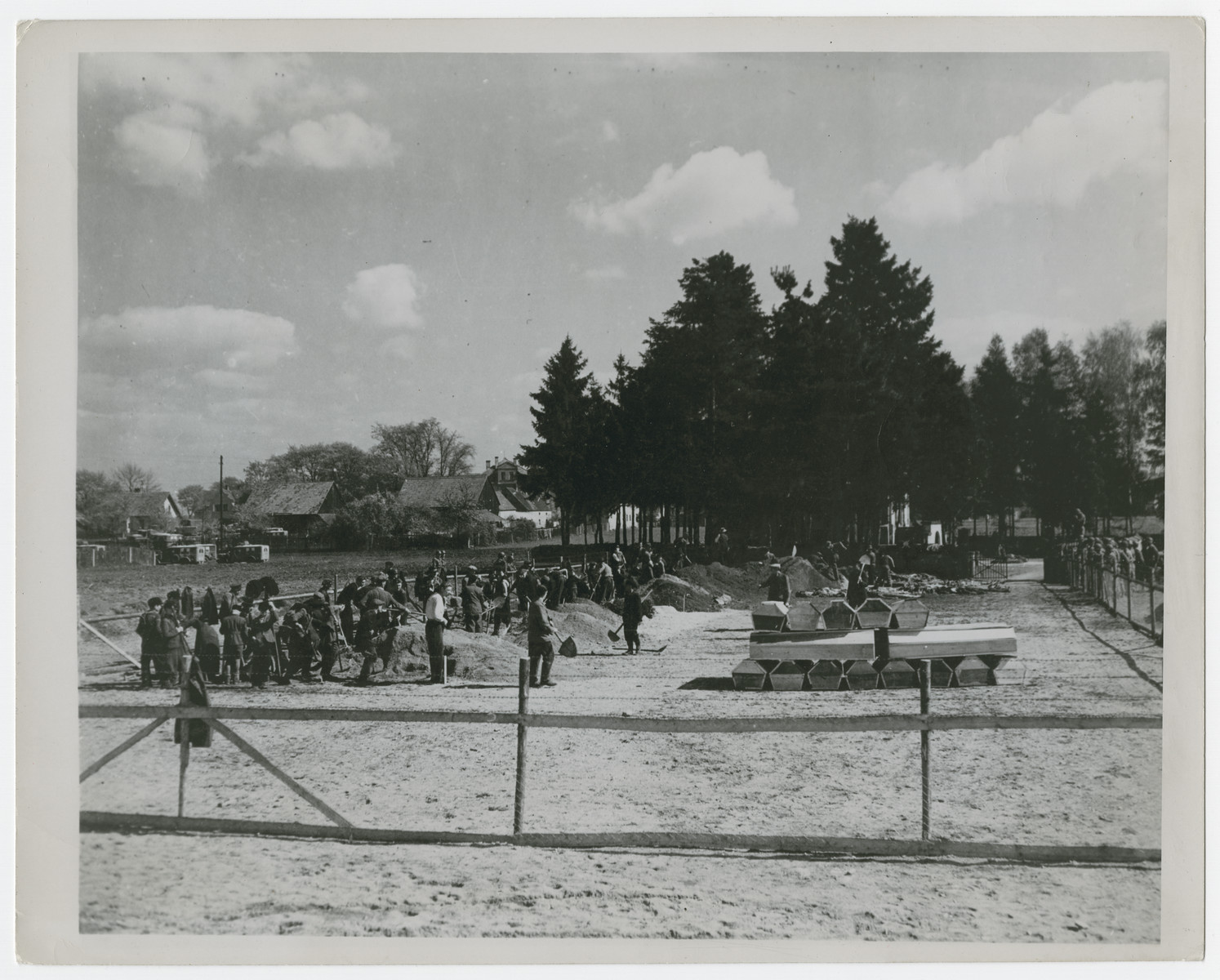 German civilians dig graves for the victims of the Schwarzenfeld atrocity under supervision of the U.S. Military Government officers.  Stacked at the right are some of the newly made coffins.