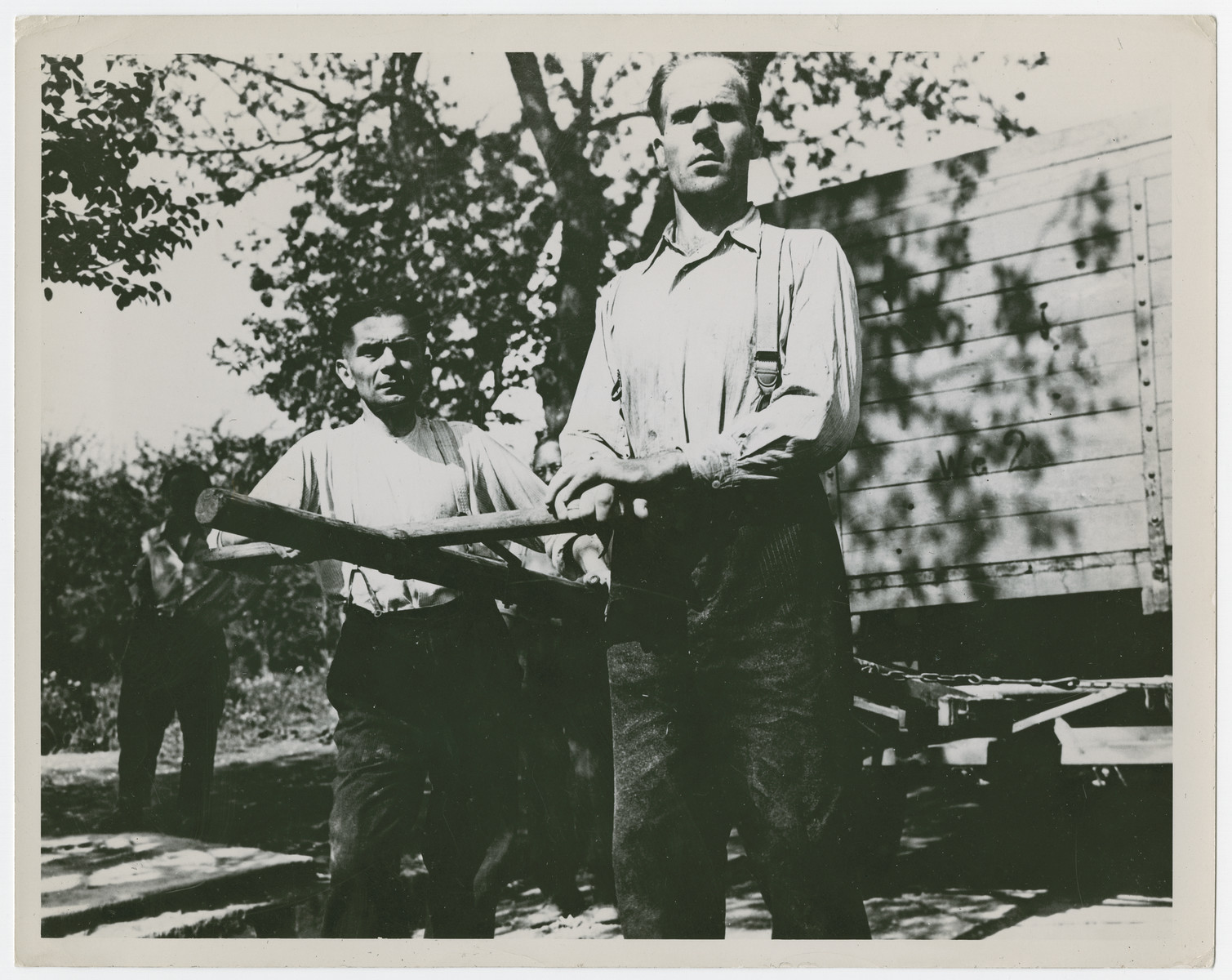 "Two former camp guards perform forced labor in the liberated Gusen concentration camp.  Original caption reads:  ""Until Camp Gusen was liberated by the Americans, these two German SS guards were hated and feared by the inmates.  Now they work under the direction of prisoners they once mistreated""."