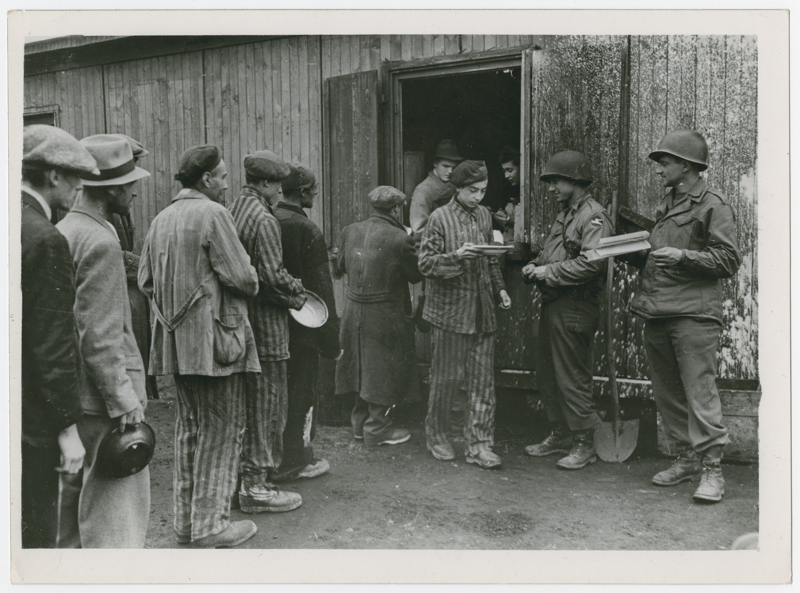 "The U.S. Troops serve soup to the liberated Jewish and Polish prisoners of the Hanover-Ahlem concentration camp.  Original caption reads:  ""U.S. Troops liberate prisoners of Nazis.  Liberated Jewish and Polish prisoners are served plates of nourishing soup at the former Nazi Hanover-Harlen concentration camp near Hanover, Germany, following capture of the city by troops of the Ninth U.S. Army, April 10, 1945.  Hanover is 155 miles west of Berlin""."