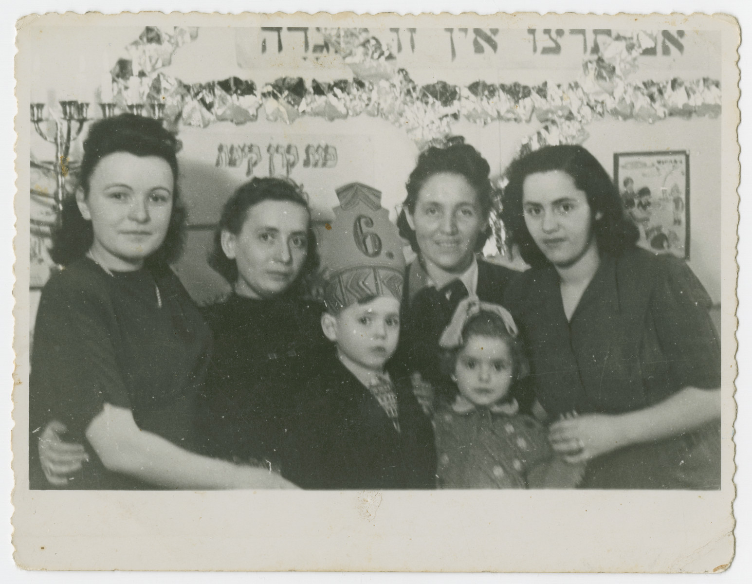 "Teachers at the Schlachtensee school pose with Joseph Fridling on the occasion of his sixth birthday.   His mother Andzia Fridling is to his left and his sister Gitla is to his right. The Hebrew banner behind them is the Zionist motto ""If you wish it, it is not a dream."""