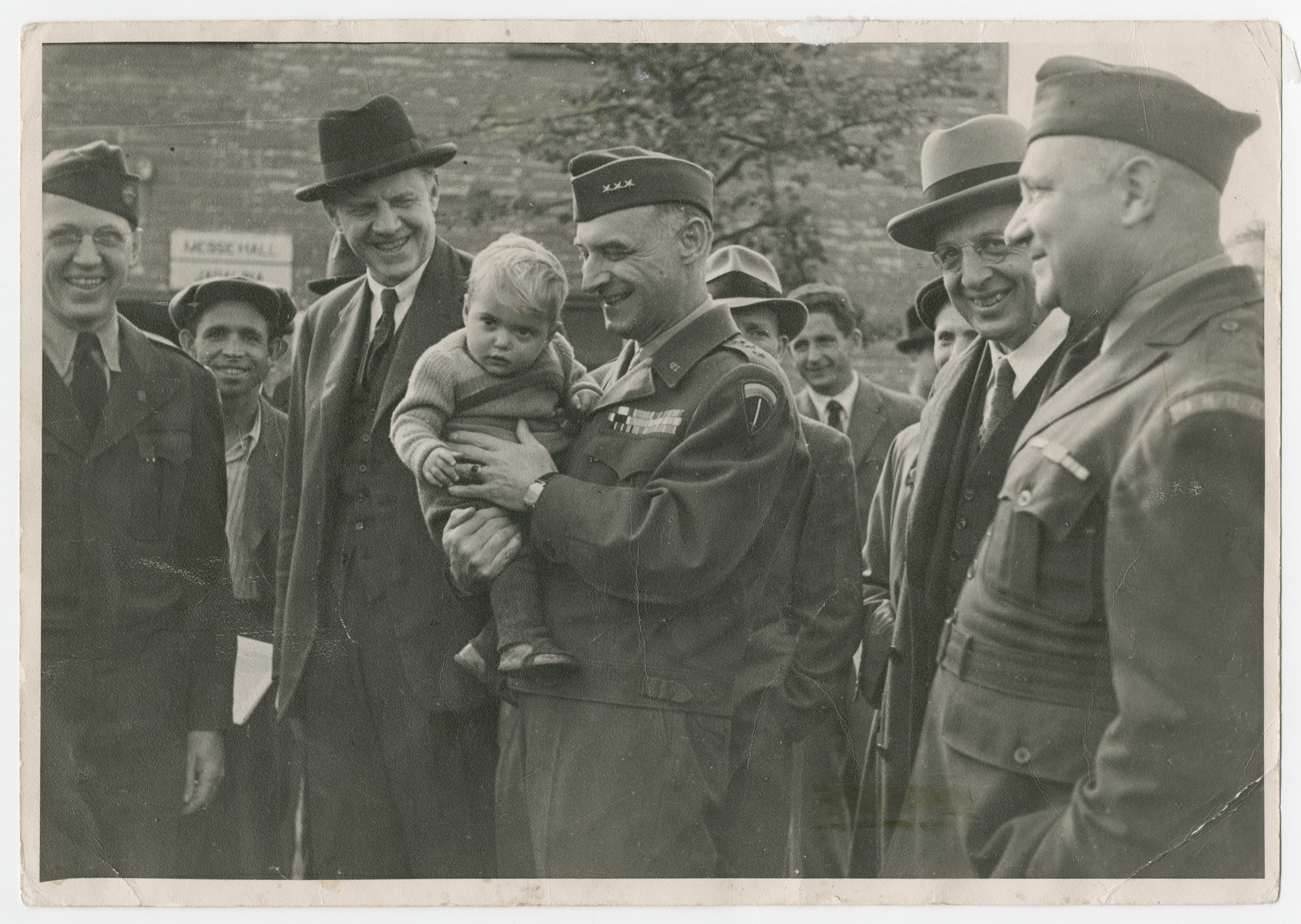 General Lucius Clay holds Gitla Fridling in his arms during a tour of the Schlachtensee displaced persons camp.  Camp director Harold Fishbein is on the far right.  Mr. Murphy from the State Dept. is probably to the left of Gen. Clay.