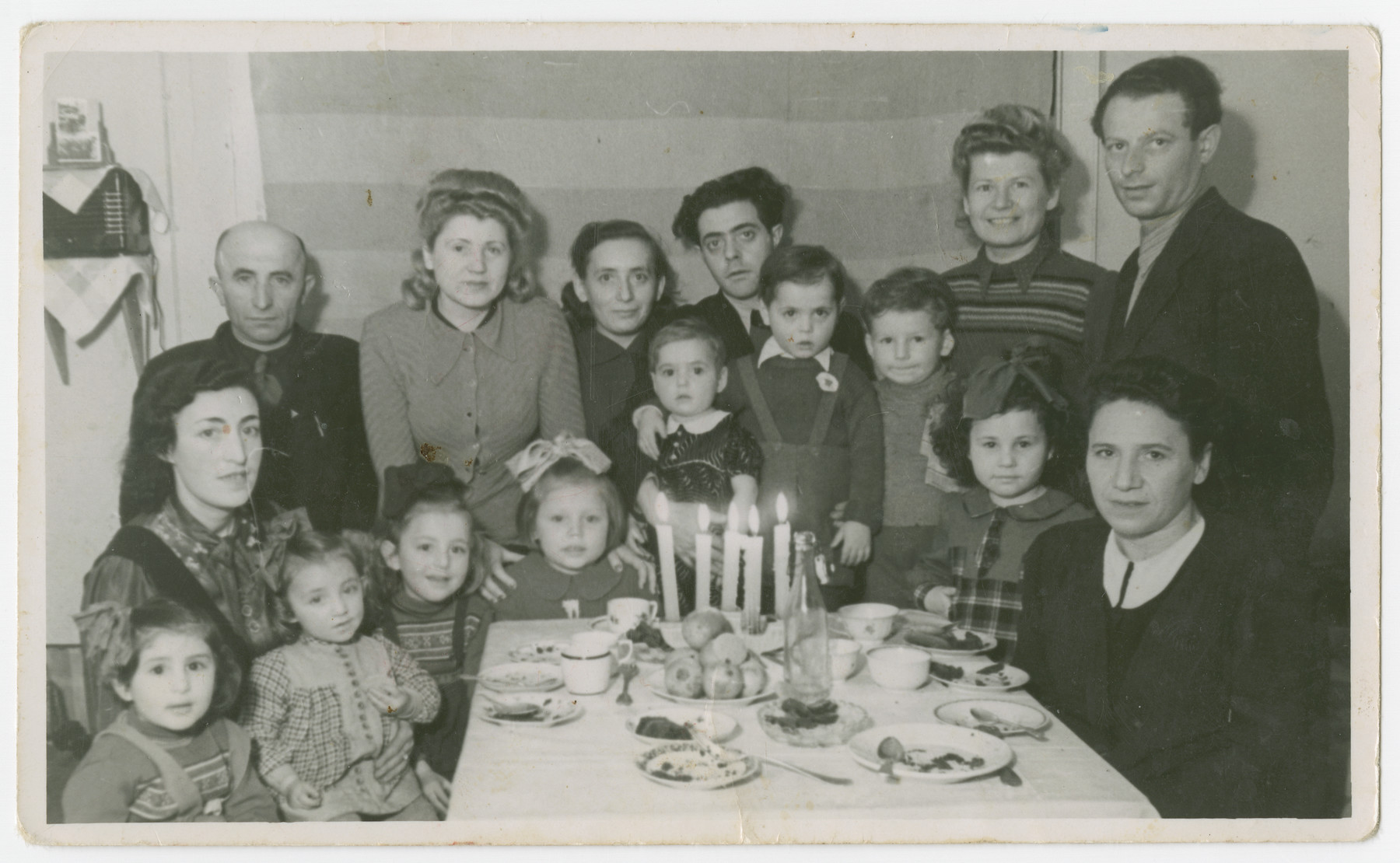 Adults and children celebrate in the Schlachtensee displaced persons camp.  [This is possibly Joseph Fridling's fifth birthday party.]  Among those pictured are standing in the back row (left to right) Abe Fridling (cousin of donor's father with the same name), unidentified, Andzia (Chana) Fridling, Gitla Fridling, Abe Fridling, Joseph Fridling and Zach Altman (far right).