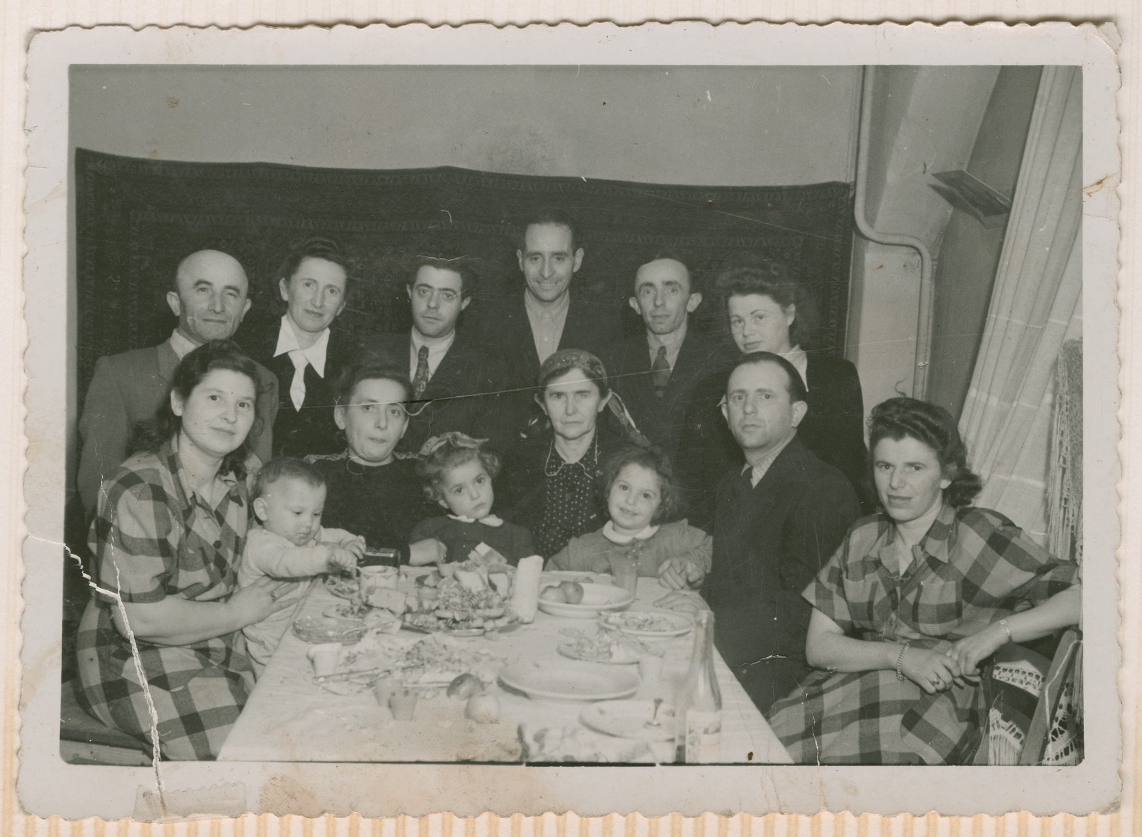 A group of men, women and children gather for a meal in the Schlachtensee displaced persons camp.