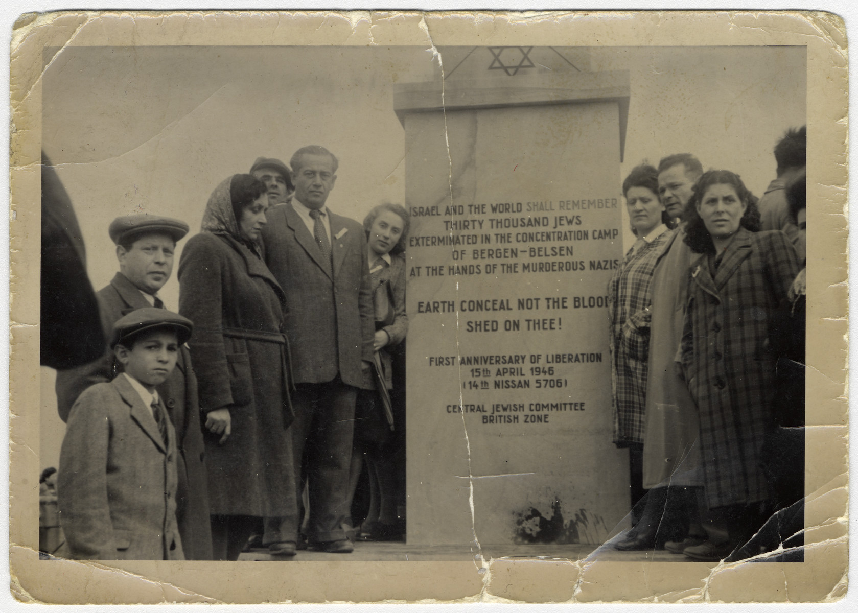 Survivors pose by the Bergen-Belsen memorial.  Standing on the left side: Man-wearing cap next to boy with cap is Mr. Srulek  Schwartzbaum (he became a furrier in Montreal, Canada); the fourth gentleman up, wearing a pin on his lapel is Elias Rosengarten.  The woman next to the monument wearing a white blouse is Esther Rosengarten.