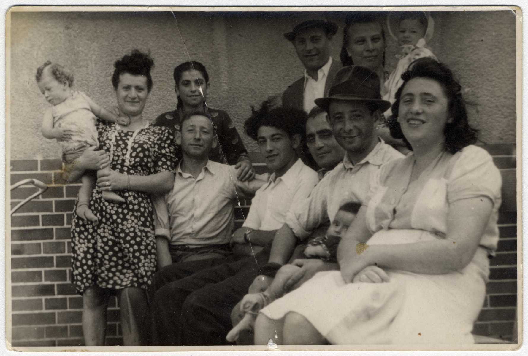 Group portrait of men and women holding young children in the Bergen-Belsen displaced persons camp.  Esther Rosengarten is pictured on the left in the polka dot dress, holding her son Aaron Rosengarten.