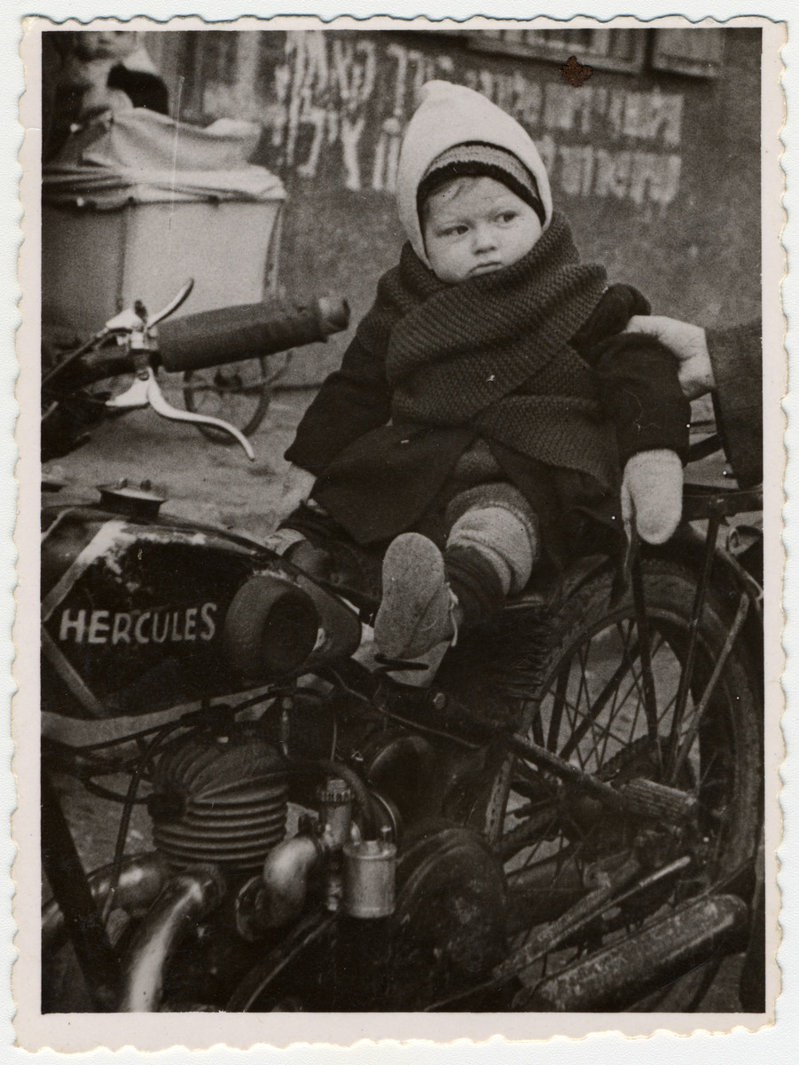 One-year-old Max Beer poses on top of a motorcycle in the Pocking displaced persons' camp.