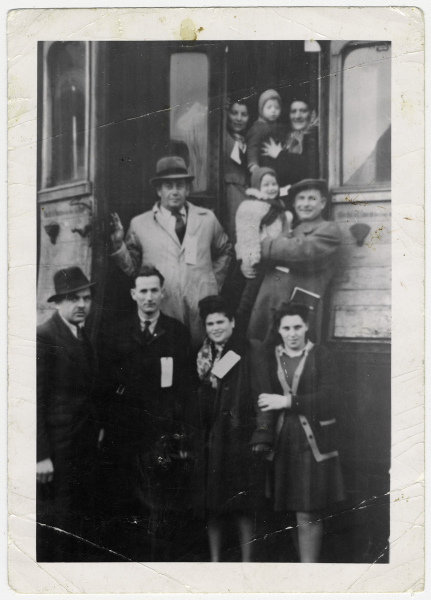 Men and women, many wearing name tags, gather by a train carriage as they prepare to emigrate.  Standing on the right side: The gentleman holding the white coated baby is Leon Bienstock with his baby daughter Chaja.  Above him, the woman wearing a kerchief, holding her baby boy (Aaron Rosengarten) is Esther Rosengarten  Standing on the left side: The gentleman, wearing the white coat and hat, holding the train door is Elias Rosengarten; above him, the woman wearing a scarf is Regina Bienstock.