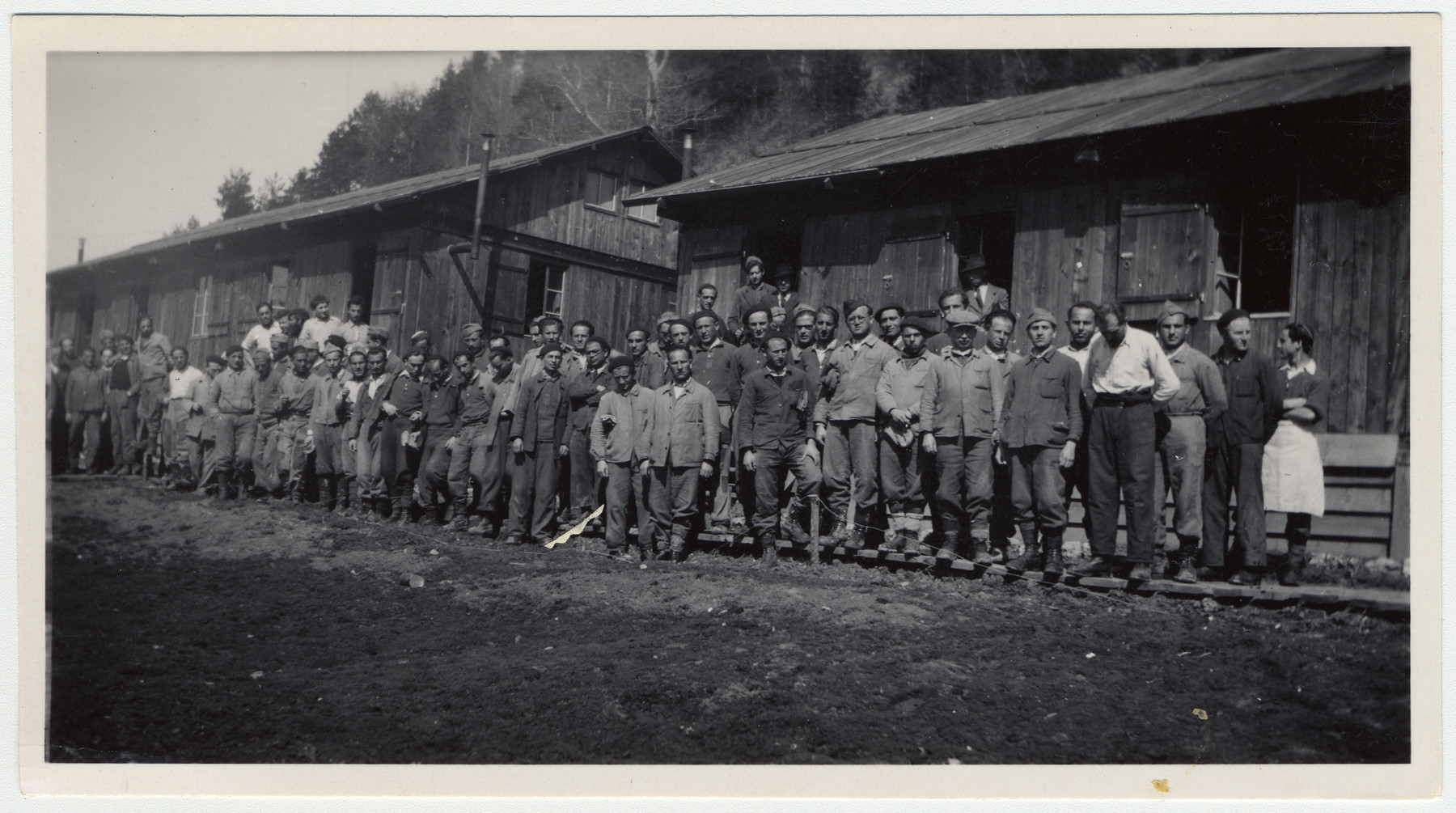 Group portrait of Jewish internees in an unidentified Swiss labor camp.  Max Schattner is pictured in the back in row standing underneath the middle window on the right, wearing a black cap.