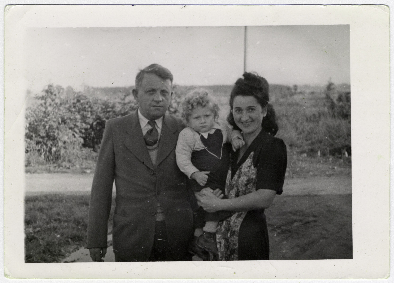 The Beer family poses outside in the Pocking displaced persons' camp.  From left to right are Leo, Max and Genia Beer.