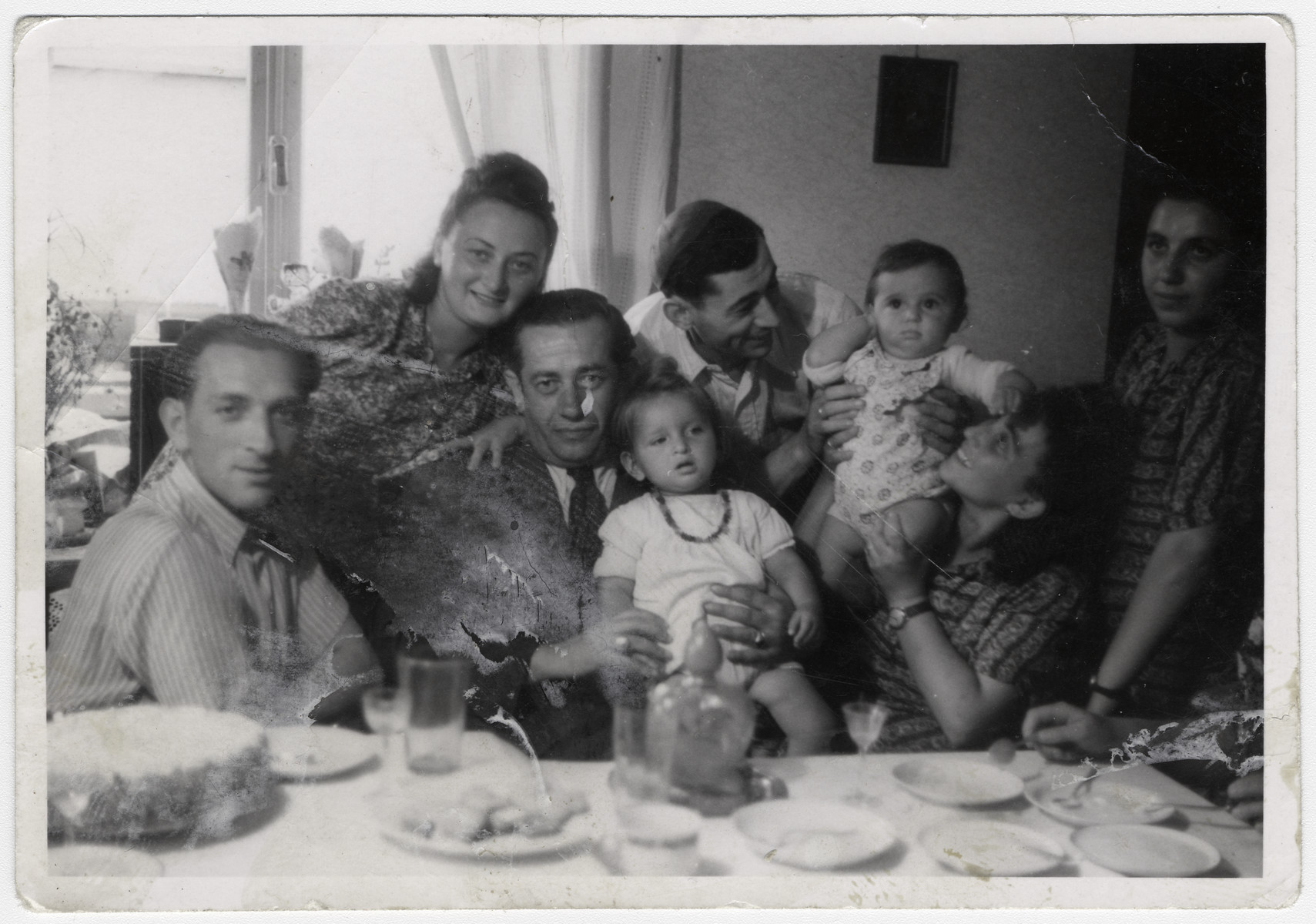 Men and women gather around a table for a celebration in the Bergen-Belsen displaced persons camp.  Left to right (sitting): The second gentleman holding the baby is Elias Rosengarten