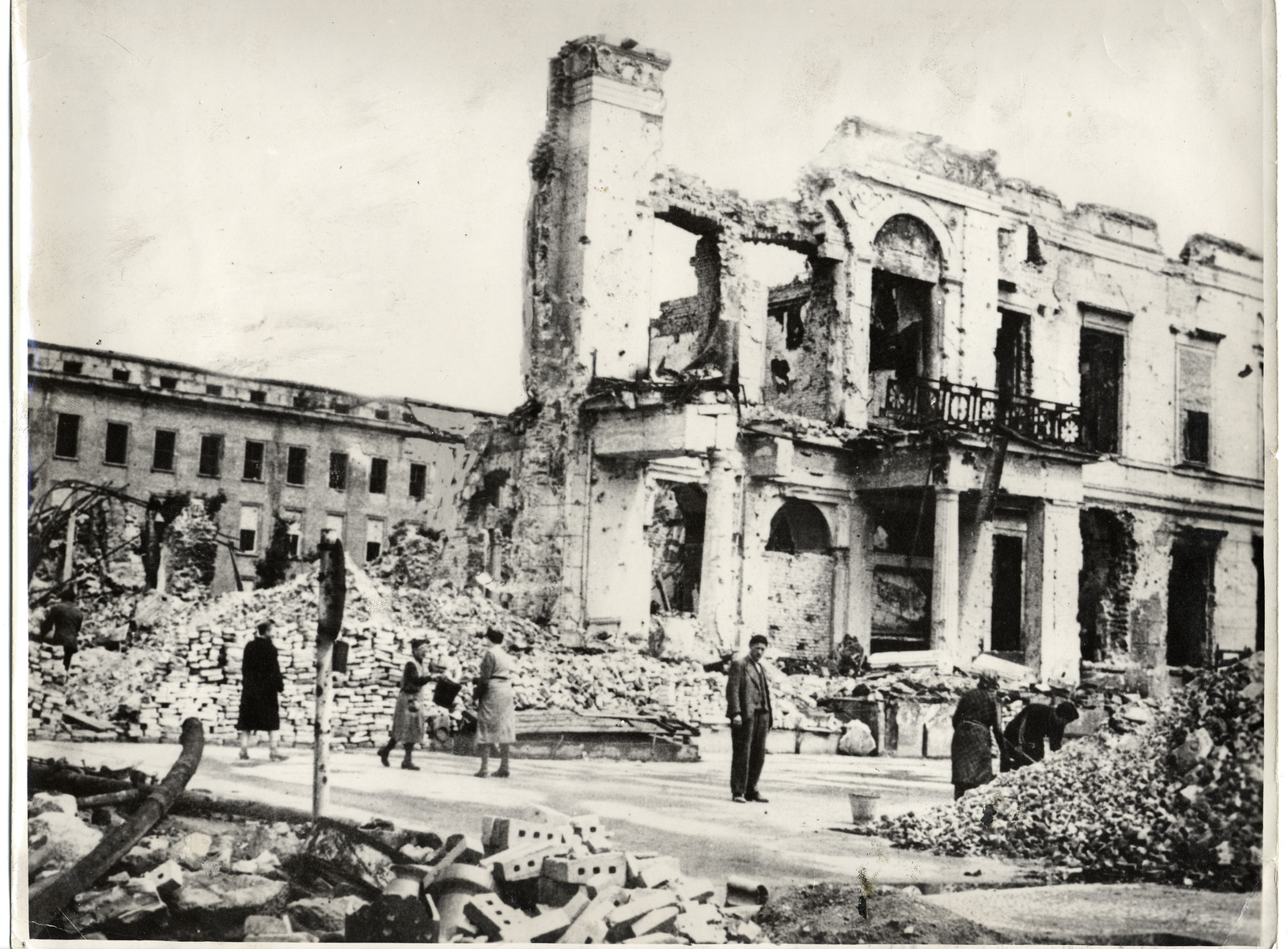 German civilians walk past the bombed out exterior of the Propaganda Ministry building on Wilhelmstrasse.