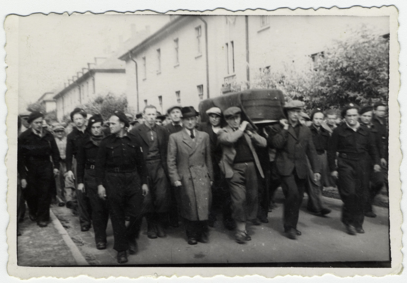 Jewish police accompany pall bearers during a funeral in the Bergen-Belsen displaced persons camp.  The pallbearer in front on the left side, wearing the shorter pants, with his right arm crossing his chest is Elias Rosengarten.