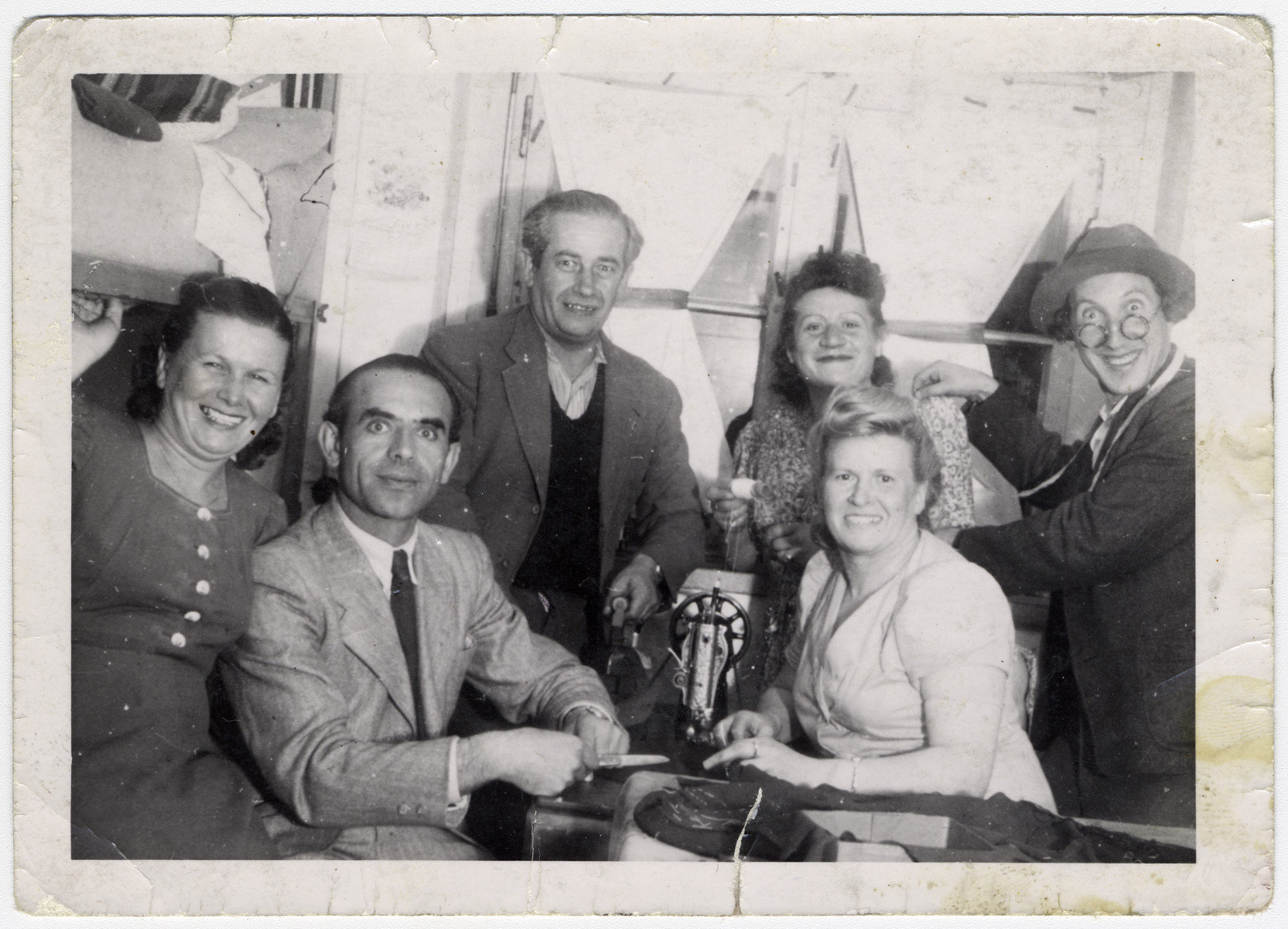Group portrait of men and women in a sewing workshop in the Bergen-Belsen displaced persons camp.  Left to right (in the back): Elias Rosengarten (my father); Esther Rosengarten (my mother)