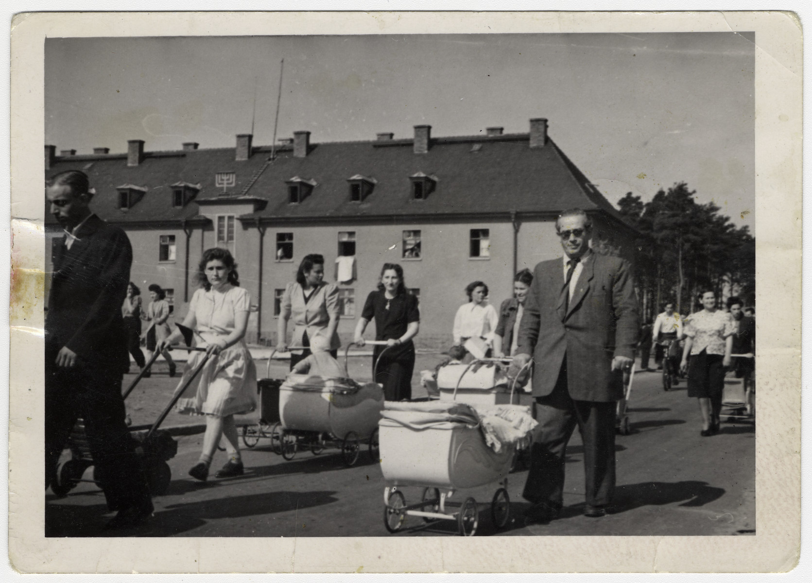 Men and women walk through the central plaza of the Bergen-Belsen displaced persons camp pushing baby carriages.  The gentleman on the right side wearing tinted spectacles, with his right hand on the stroller is Elias Rosengarten.