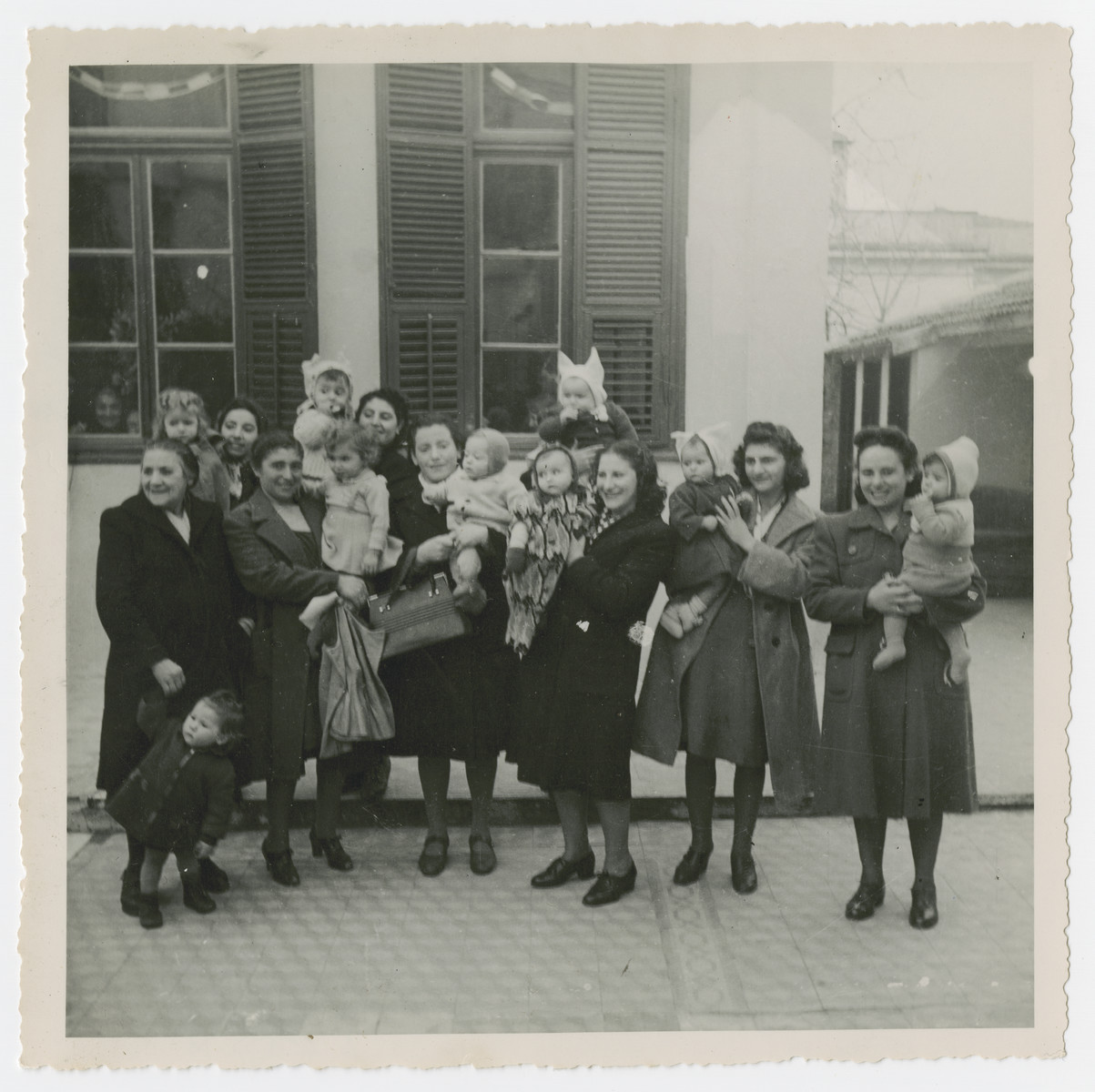 """Group portrait of Jewish women holding their babies.  Most had survived concentration camp.  The original caption reads: """"The youngest generation.  Some of these women were supposed to have been sterilized, but a Jewish doctor, an unsung hero, didn't do as he was told and was tossed into the gas chamber as a result."""""""