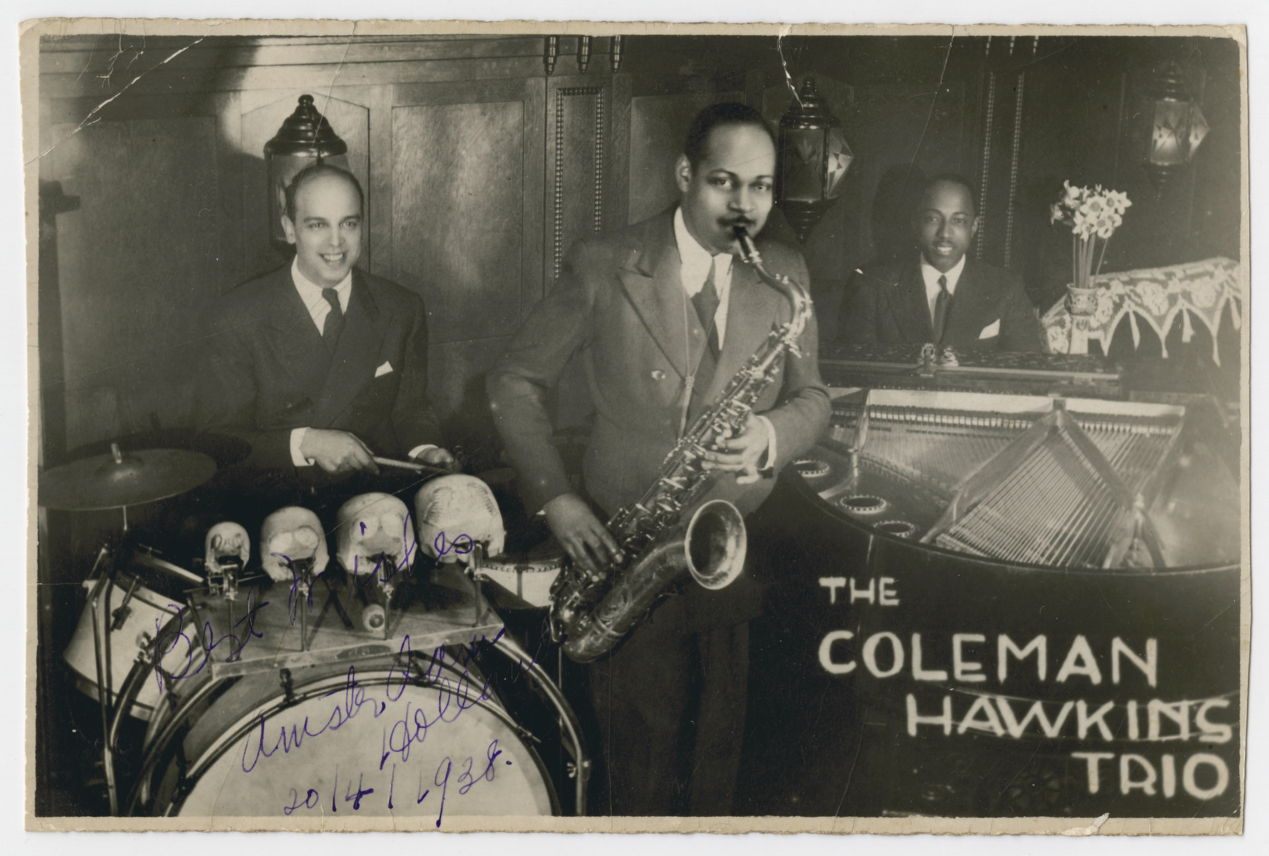 "The Coleman Hawkins jazz trio performs in Amsterdam.  Pictured are Coleman Hawkins (tenor sax), Maurice van Cleef (drums) and Freddy Johnson (piano).  The original caption reads: ""To Aunt Hattie, In remembrance of all her kindness to my family and self.  I shall never forget it, Freddy."""