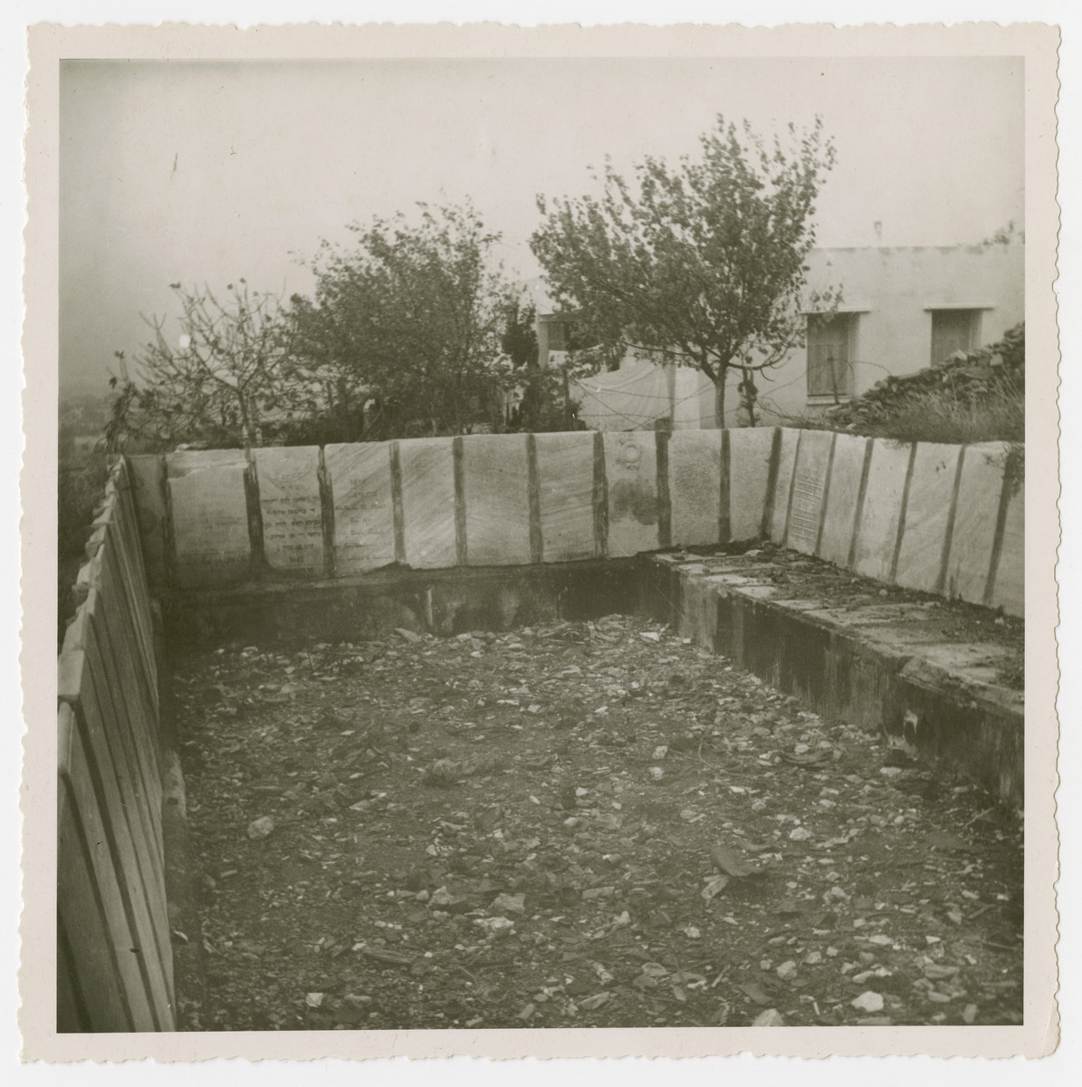 "View of a swimming pool constructed from desecrated Jewish tombstones.  The original caption reads: ""Gravestones put up by Germans as a swimming pool."""