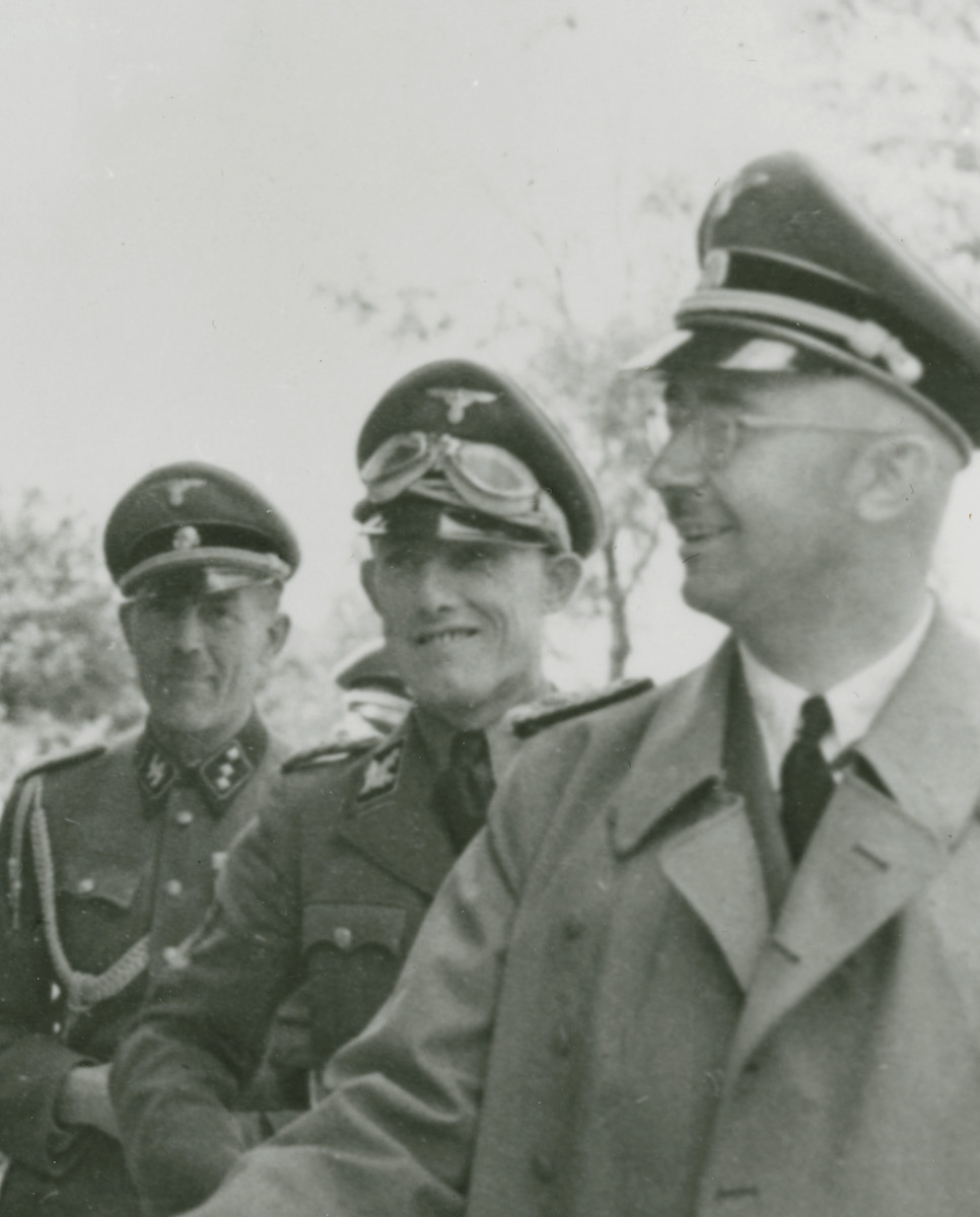 Reichsfuehrer SS Heinrich Himmler (right) shakes the hand of camp commandant Friedrich Warzok during an official tour of a Jewish labor camp along the main supply route in Galicia.  Also pictured is SS-Gruppenfuhrer Fritz Katzmann (immediately behind Himmler).