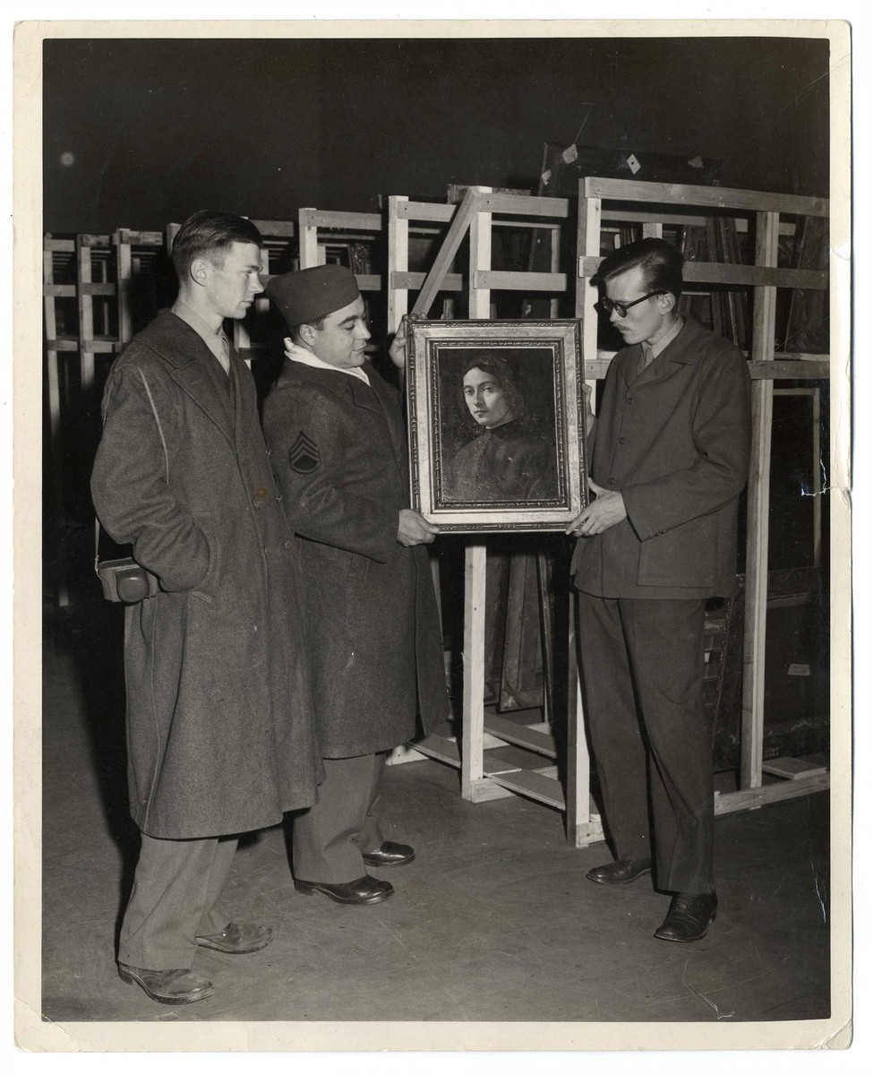 Examination of one of the framed paintings that was looted by the Nazi regime in an underground vault.  Pictured on the left is Sargeant James Reeds.
