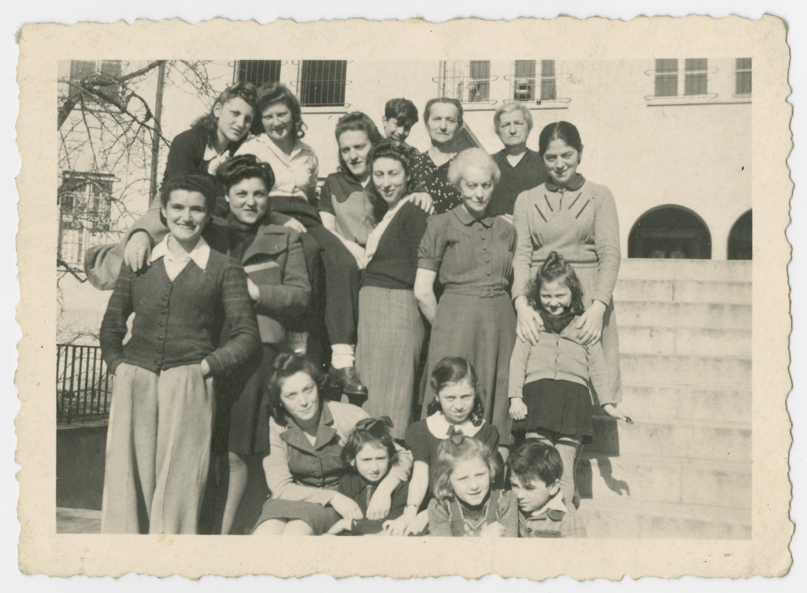 Group portrait of women and girls standing on the steps of what probably is the Liebenau internment camp for foreign nationals.  Pictured on the far right are Rywa Roth with her daughter Anna.