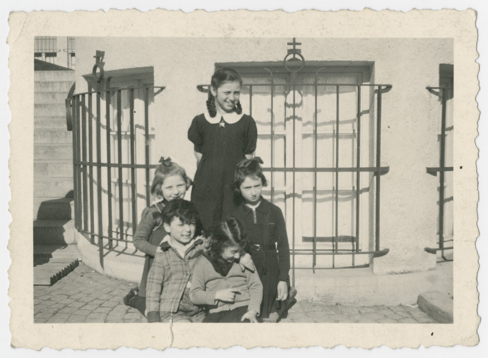 Group portrait of children probably in the Liebenau internment camp, a camp for foreign nationals.  Mina Roth is standing in the back, and her sister Anna is in the front with her head down.