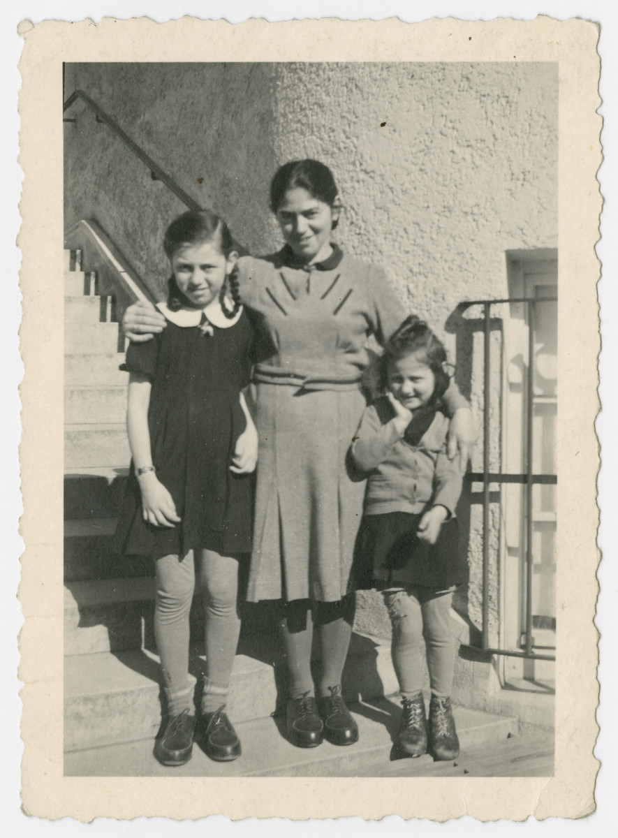 The Roth family stands on the steps of the Libenau internment camp.  Liebenau, located on Lake Constance close to Meckenbeuren, was opened in 1940 and operated until 1945.  It was used as an assembly point for prisoners who were being considered for exchange.  Pictured are Mina, Rywa and Anna Roth.