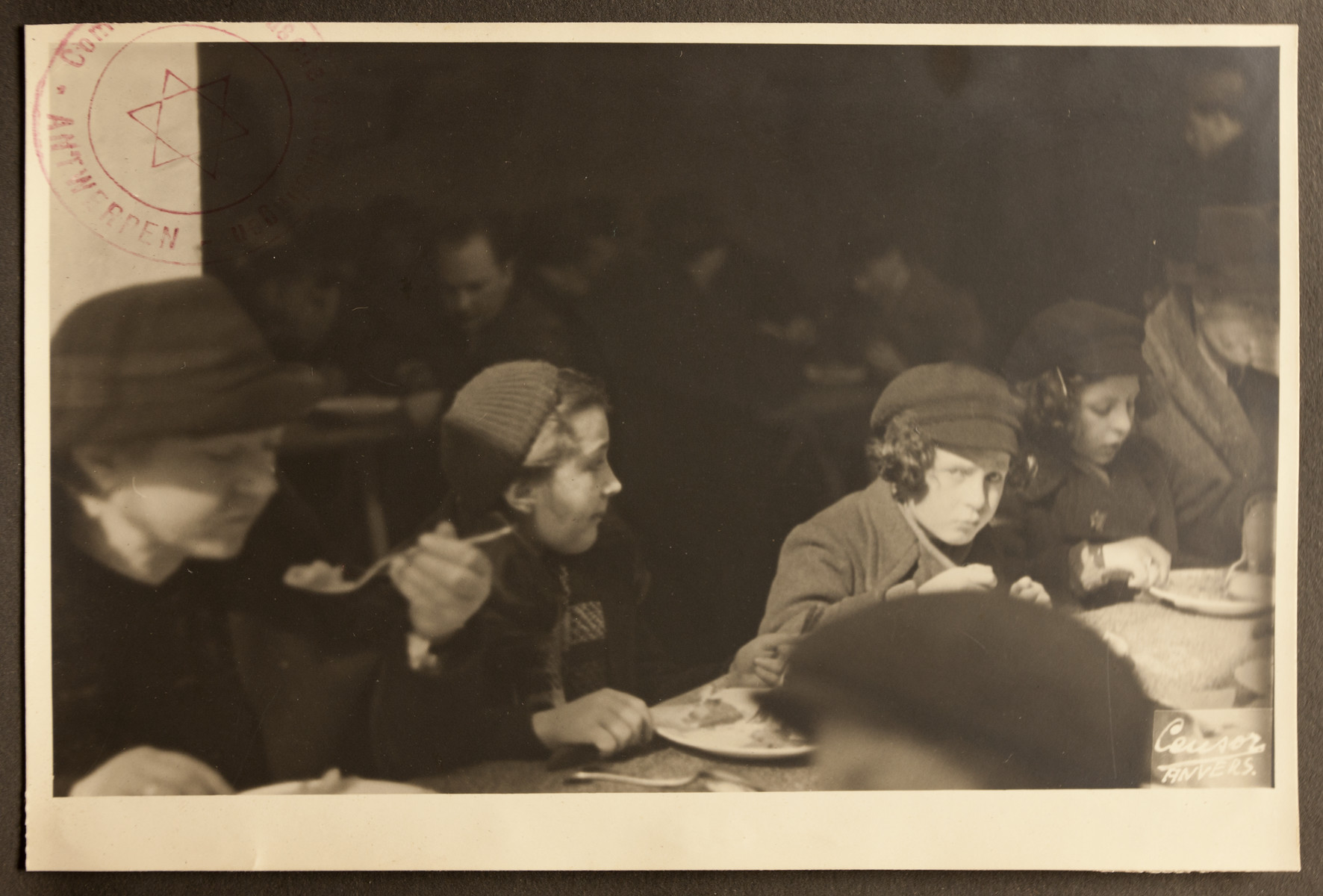 Women and children eat in the dining room of the Jewish Refugee Aid Committee of Antwerp.