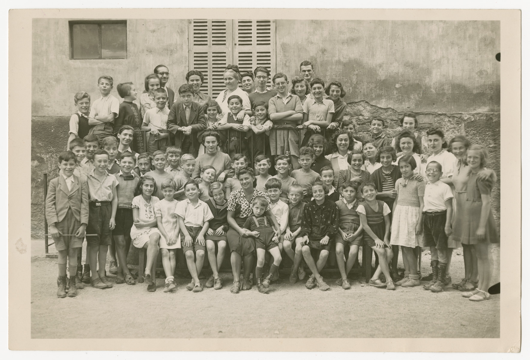 Group portrait of children standing outside of Chateau-le-Masgelier.  Among those pictured are Alice Grunewald, sitting in the front row, thrid from the right, in the dark dress.  Inge Grunewald, standing in the second row, fifth from the left, wearing a stripped top.  Lily Grunewald, standing on the balcony, on the far right, slightly behind a boy.