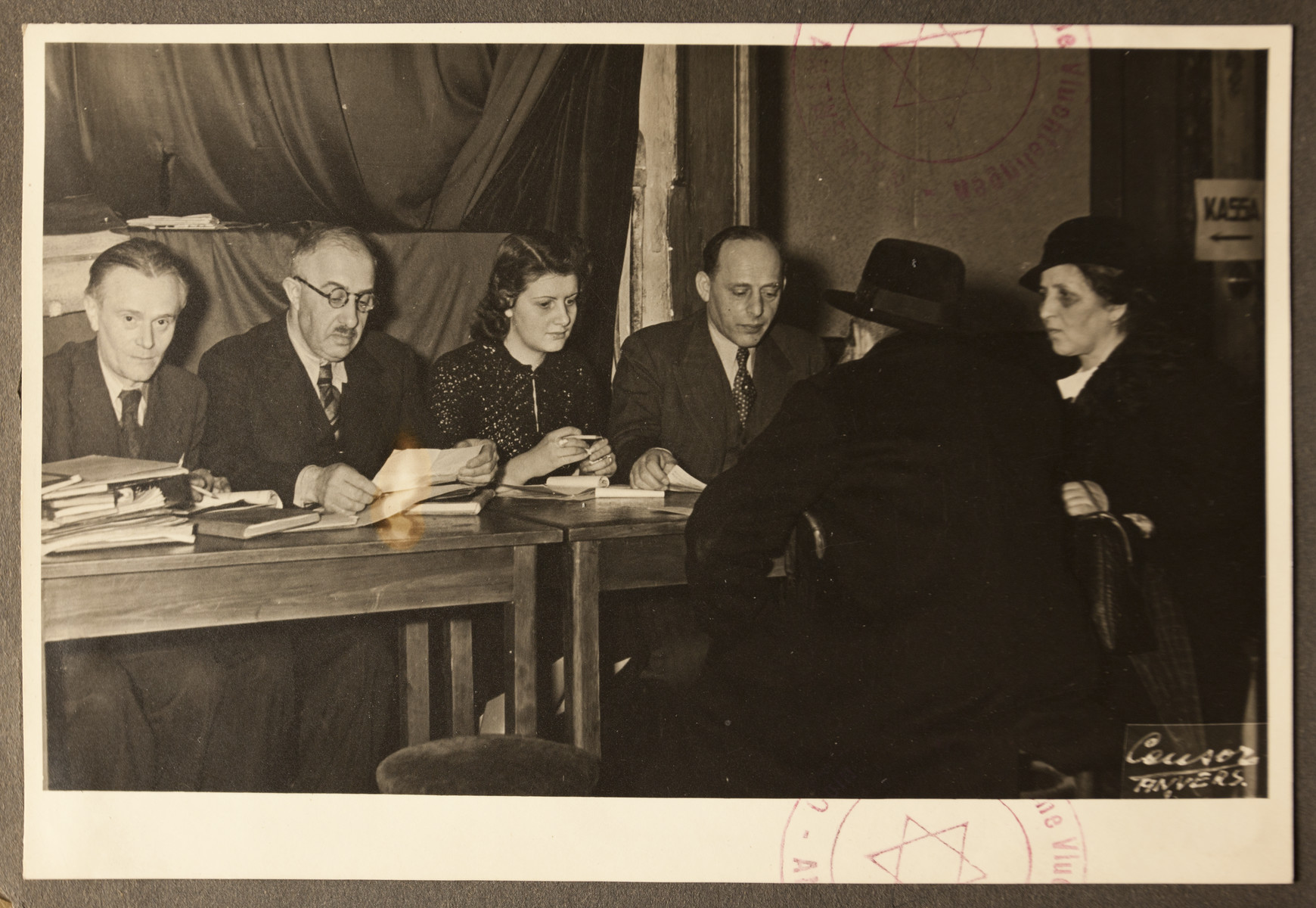 Staff of the Jewish Refugee Aid Committee of Antwerp meet with newly arrived refugees.