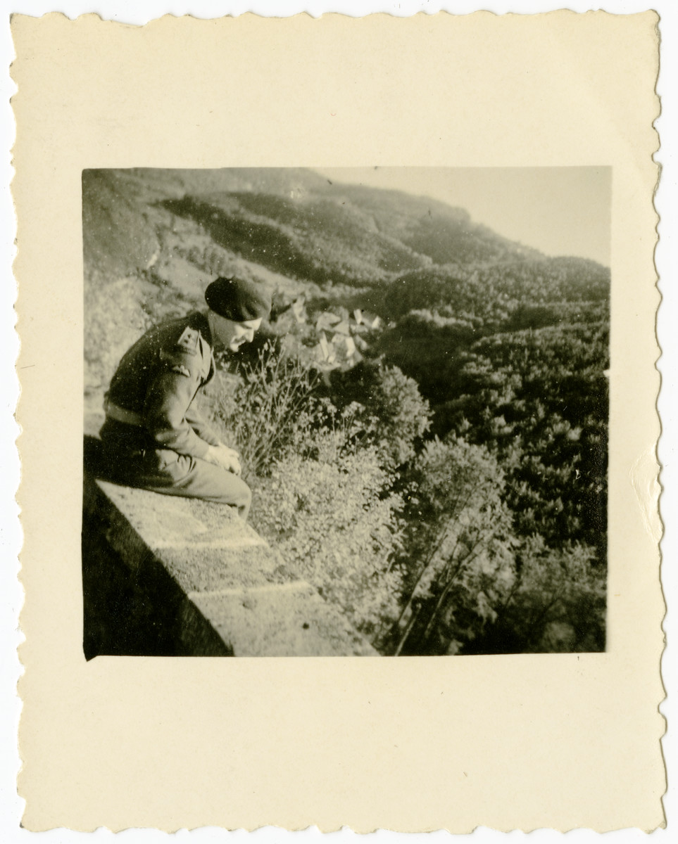 Freddy Gray (Manfred Gans) sits on a brick wall overlooking a wooded hill.