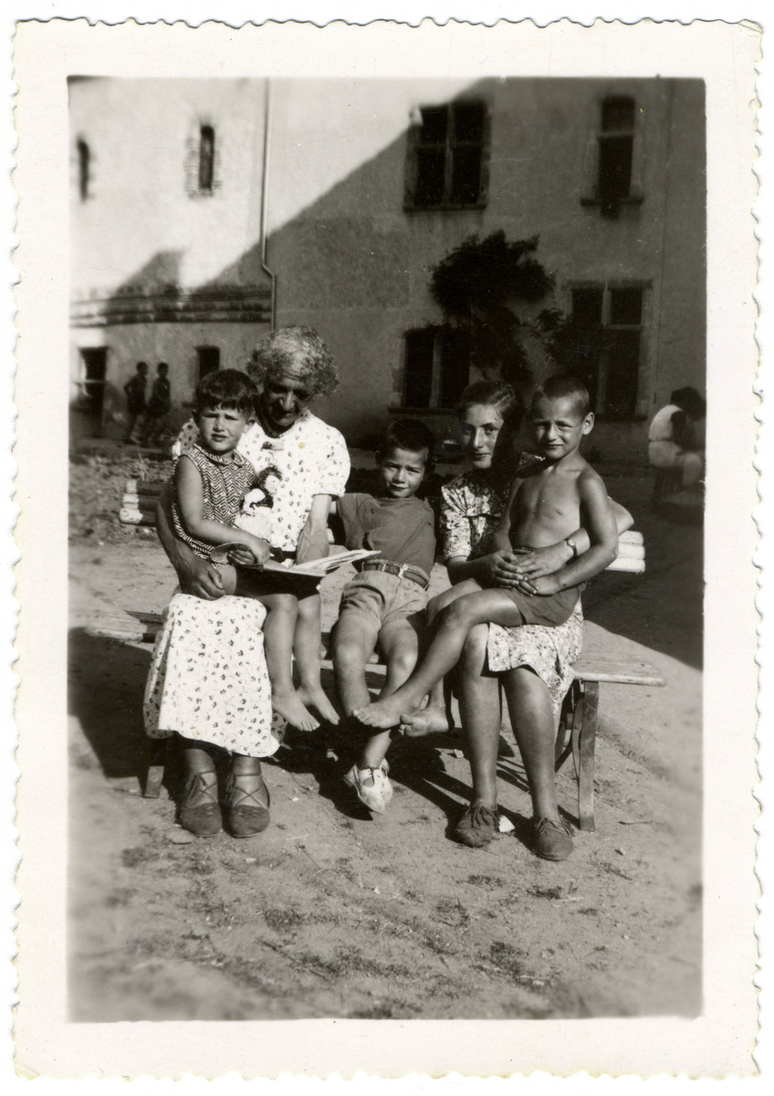 "Young children and their adult caretakers pose for a photograph at the children's home of Chateau de la Hille.  Seated, from left, Mme. Irène Frank, teacher, and caretaker Lotte Nussbaum. Children are, from left, Antoinette ""Toni"" Steuer, Henri Vos and Gustave Manasse."