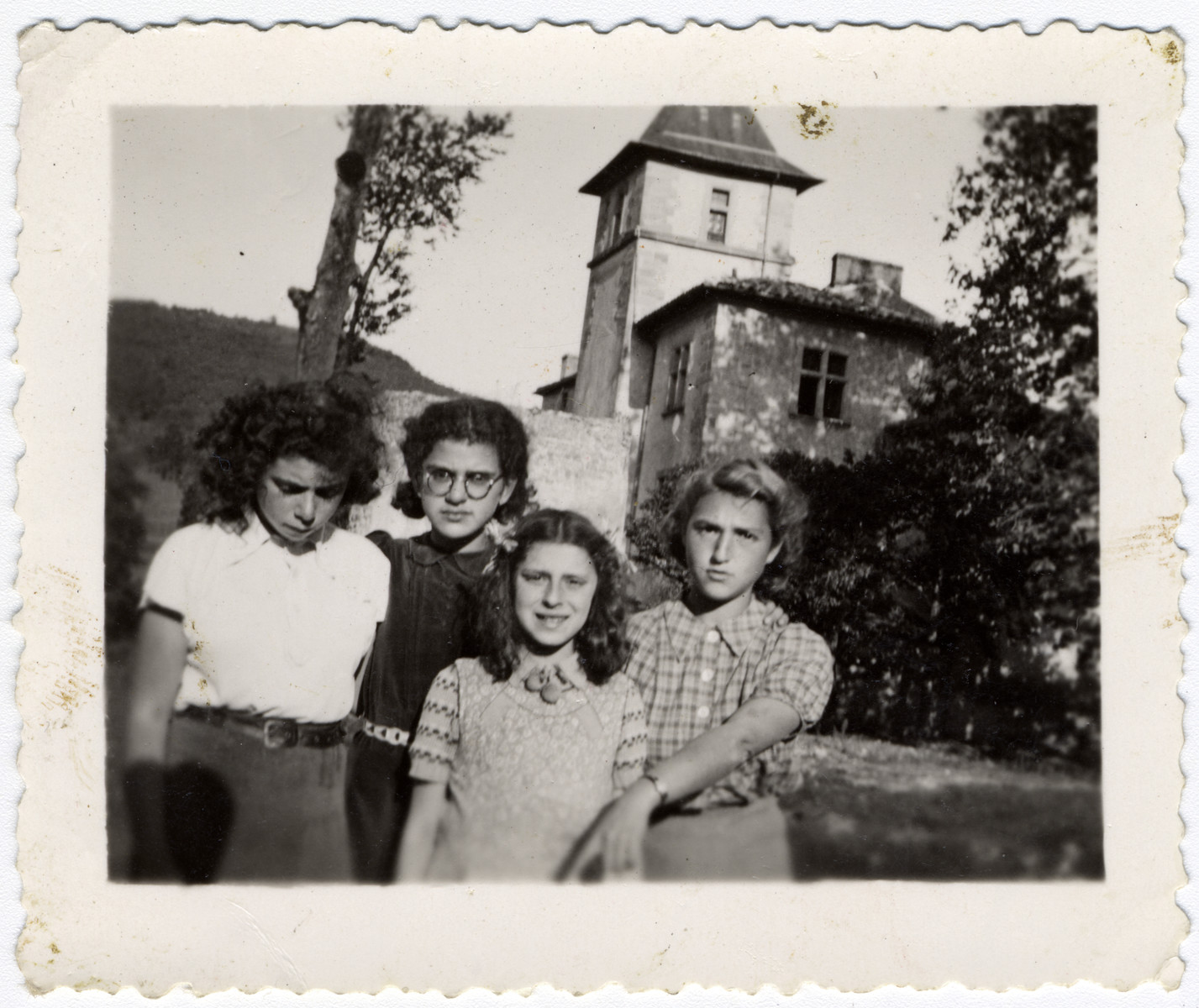 Portrait of four girls standing on the terrace of the children's home of Chateau de la Hille.  Second from left, Rosa Goldmark. Lixie Grabkowicz at right.