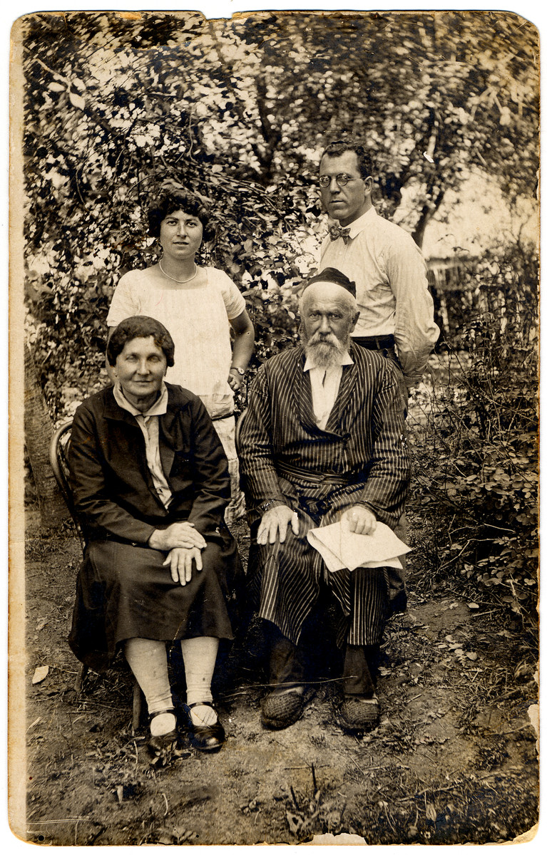Members of the Rosenthal family pose in their garden.  Pictured are Bela Rozenthal, Meir Tzvi Rozenthal, Sheindel (perished 1942) and Avraham Kleiman (survived).
