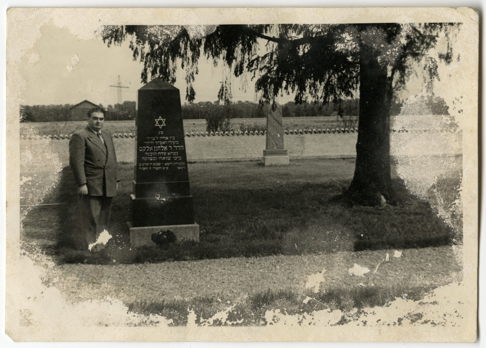 "Hans Malbin stands next to the memorial to his brother-in-law Dr. Elkhanan Elkes, which he helped erect in the Jewish cemetery of Landsberg.  The text reads ""Here rests among his Brethren in Sorrow our Dear Husband and Father, Dr. Elkhanan Elkes, Head of the Community of Kovno in Times of Peril and Mortal Danger."""