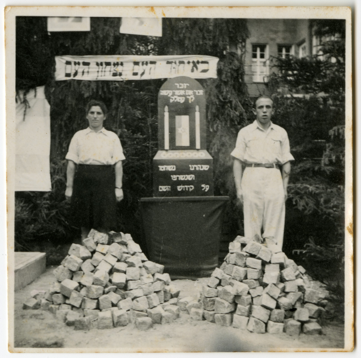 "A man and woman stand guard by a memorial to the victims of the Holocaust. [possibly in New Palestine]  The banner on the top reads i""n the unity of the people is the victory of the people"", and the memorial says to ""remember what Amalek did to you."""