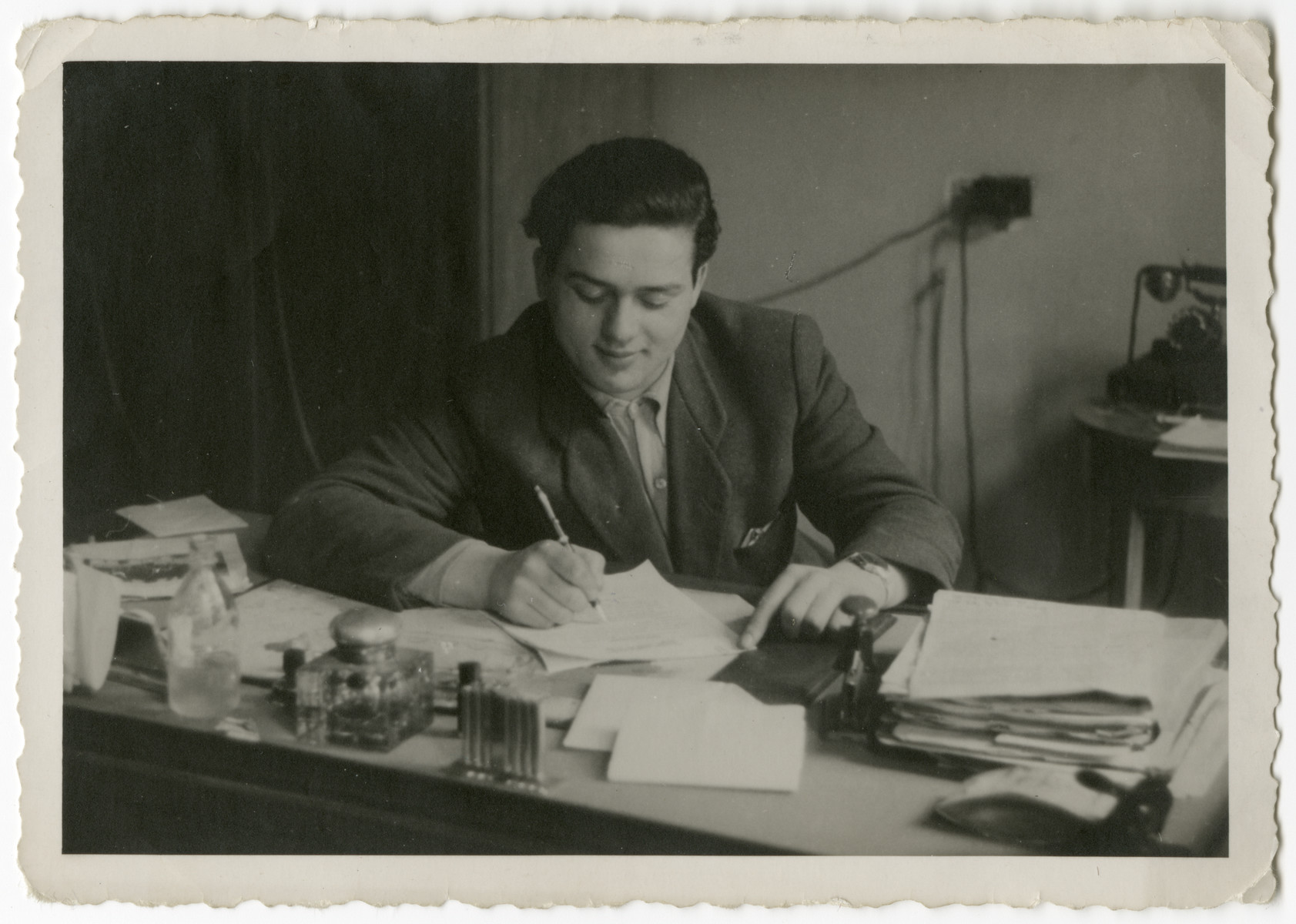 Izack [last name unidentified] works at a desk in the Salzburg displaced persons camp.