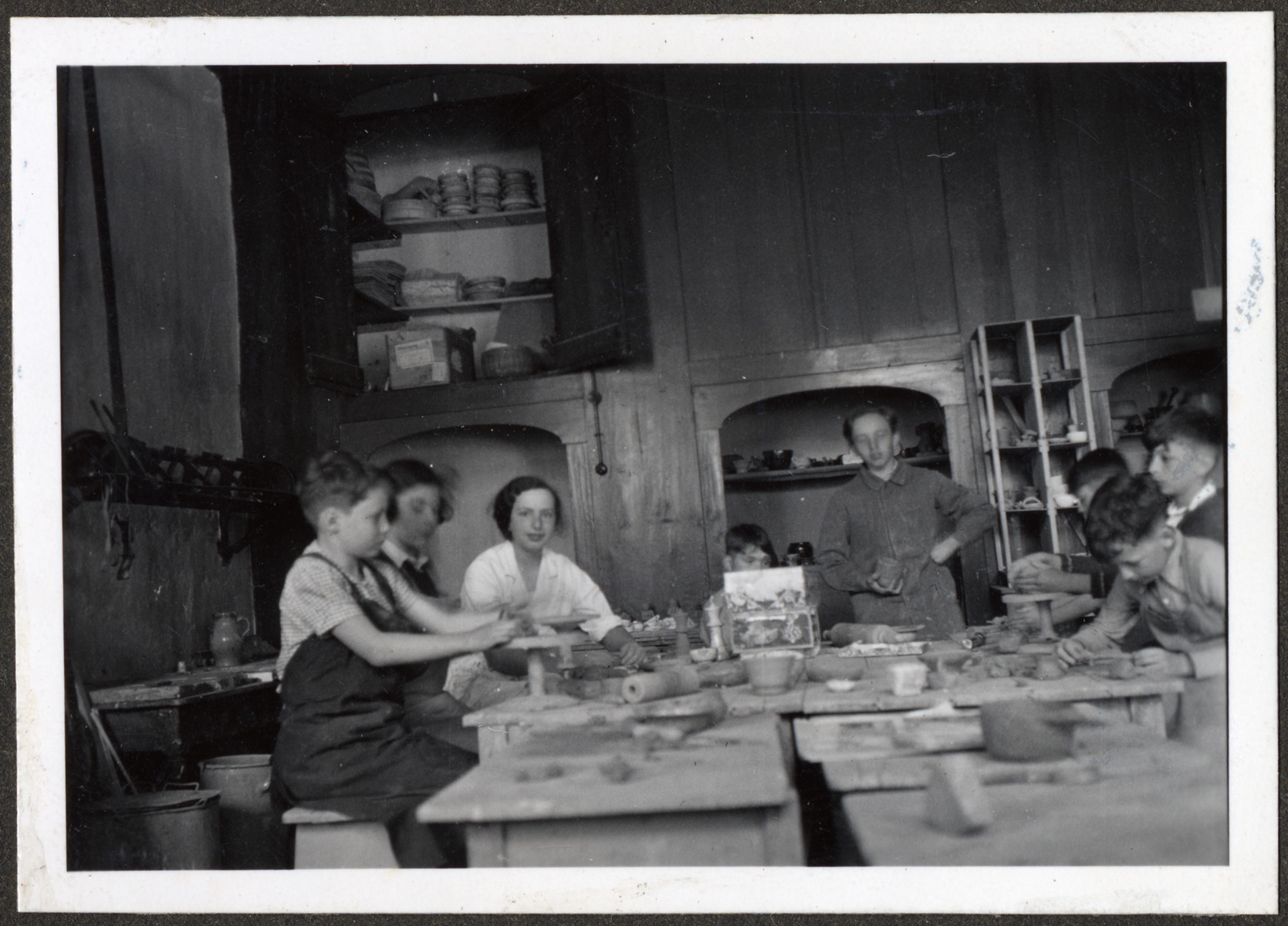 Children, many of them German Jewish refugees, make pottery in an art class at a Quaker boarding school in Eerde.