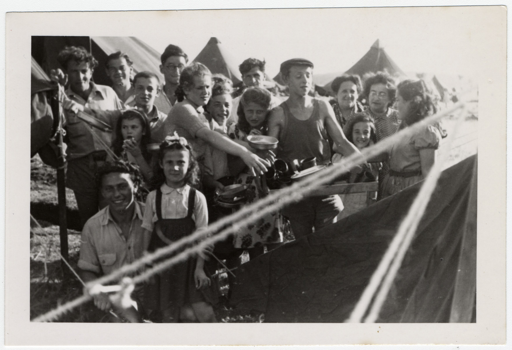 Jewish displaced persons pose outside tents [probably in Cyprus].