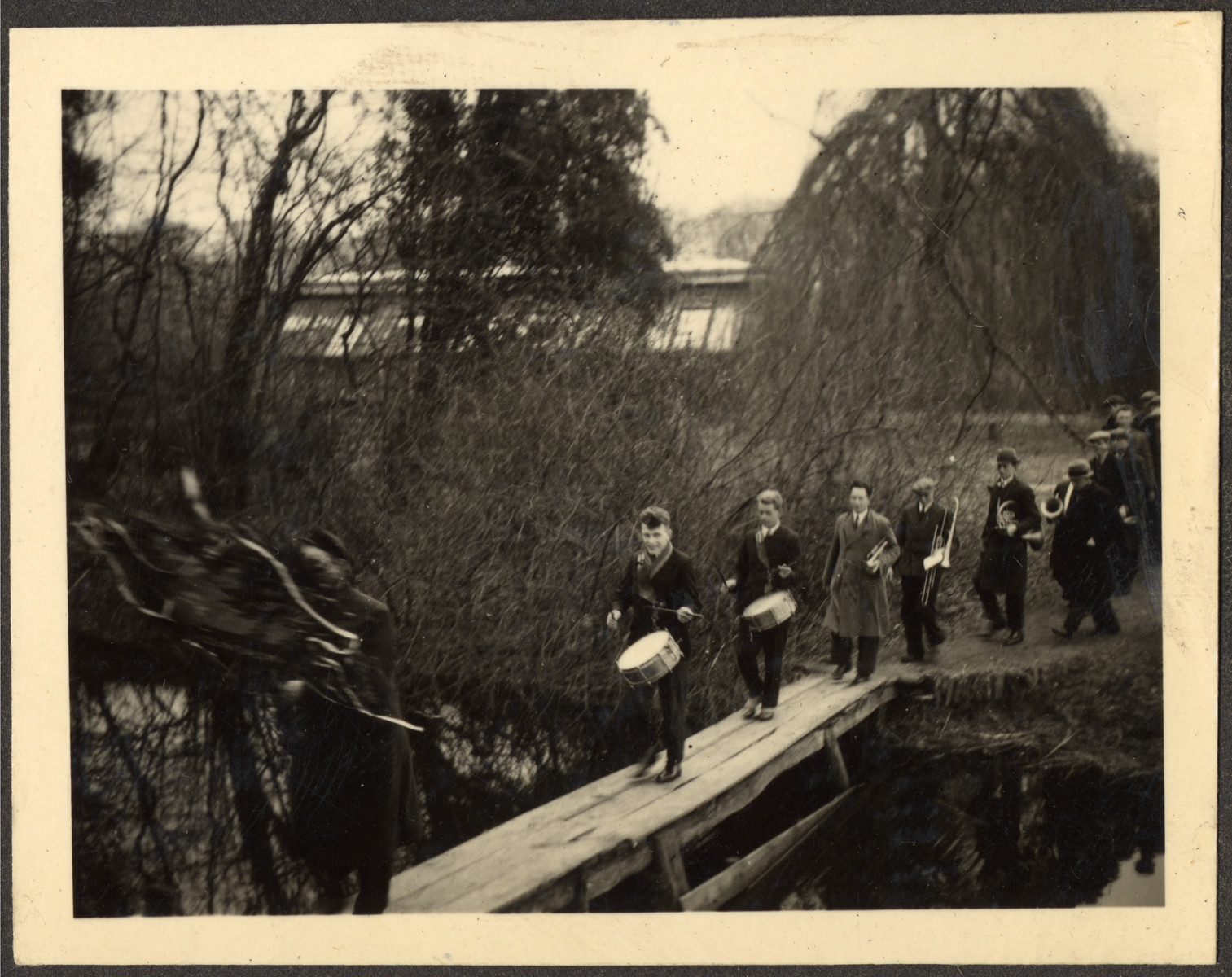 Students many of them German Jewish refugees, march with muscial instruments across a pedestrian bridge at a Quaker boarding school in Eerde.