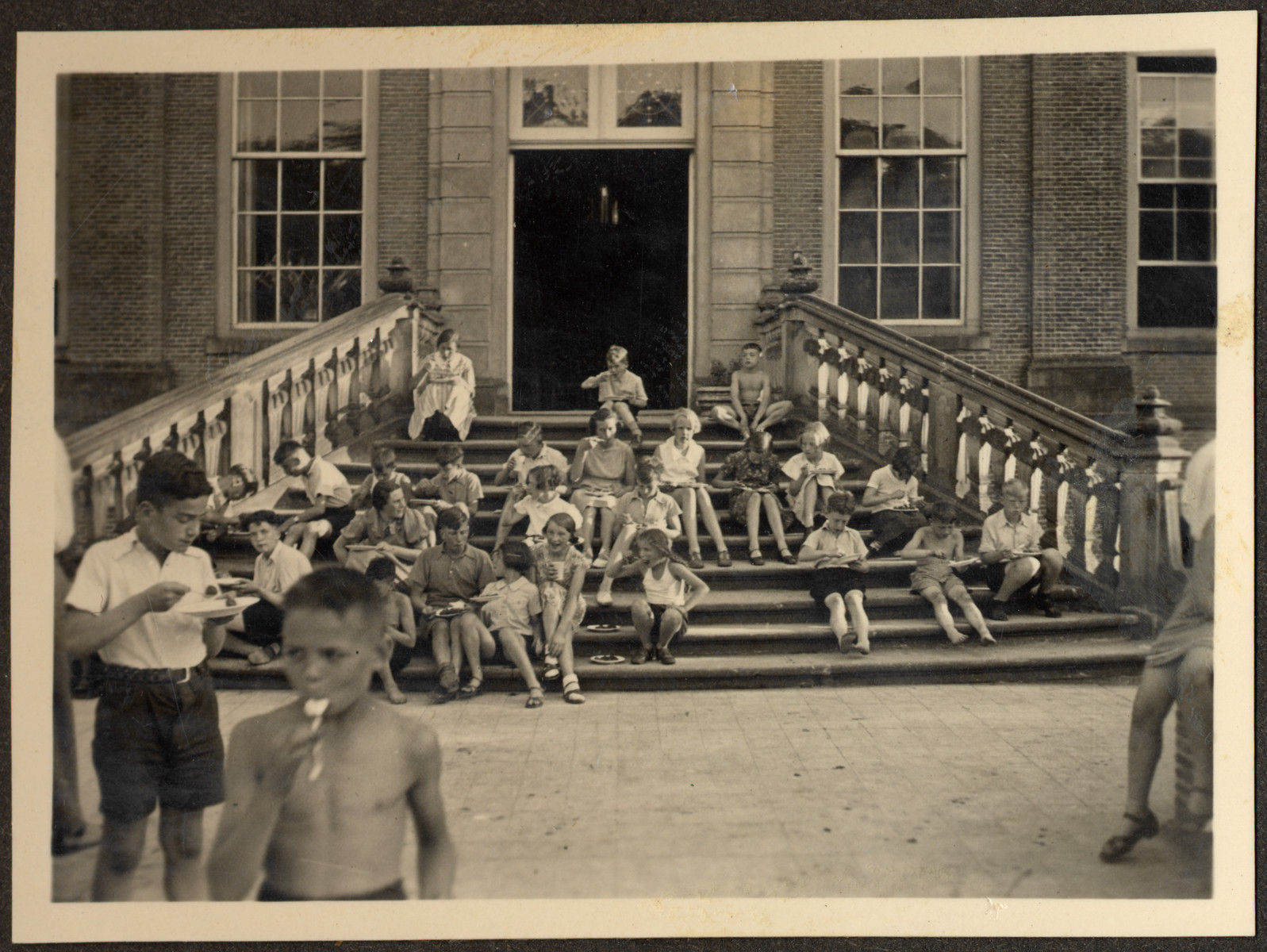 Children, many of them German Jewish refugees, relax on the steps of a Quaker boarding school in Eerde.