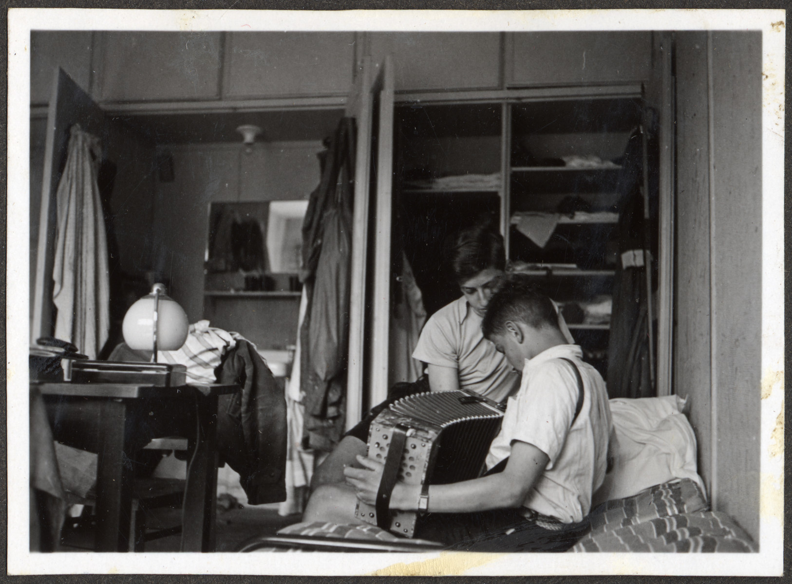 Two teenagers, probably German Jewish refugees, play accordion and relax in their dorm room in a Quaker boarding school in Eerde.
