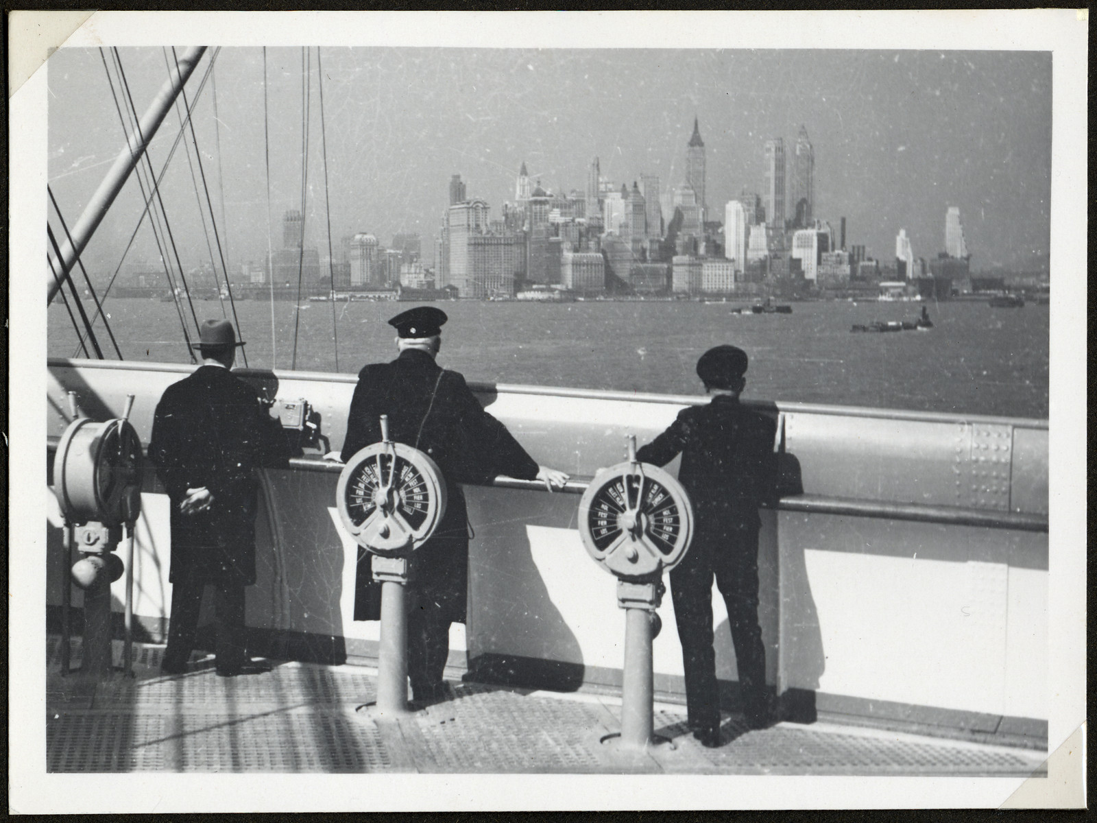 A ship pulls into New York harbor; the skyline can be seen in the background.