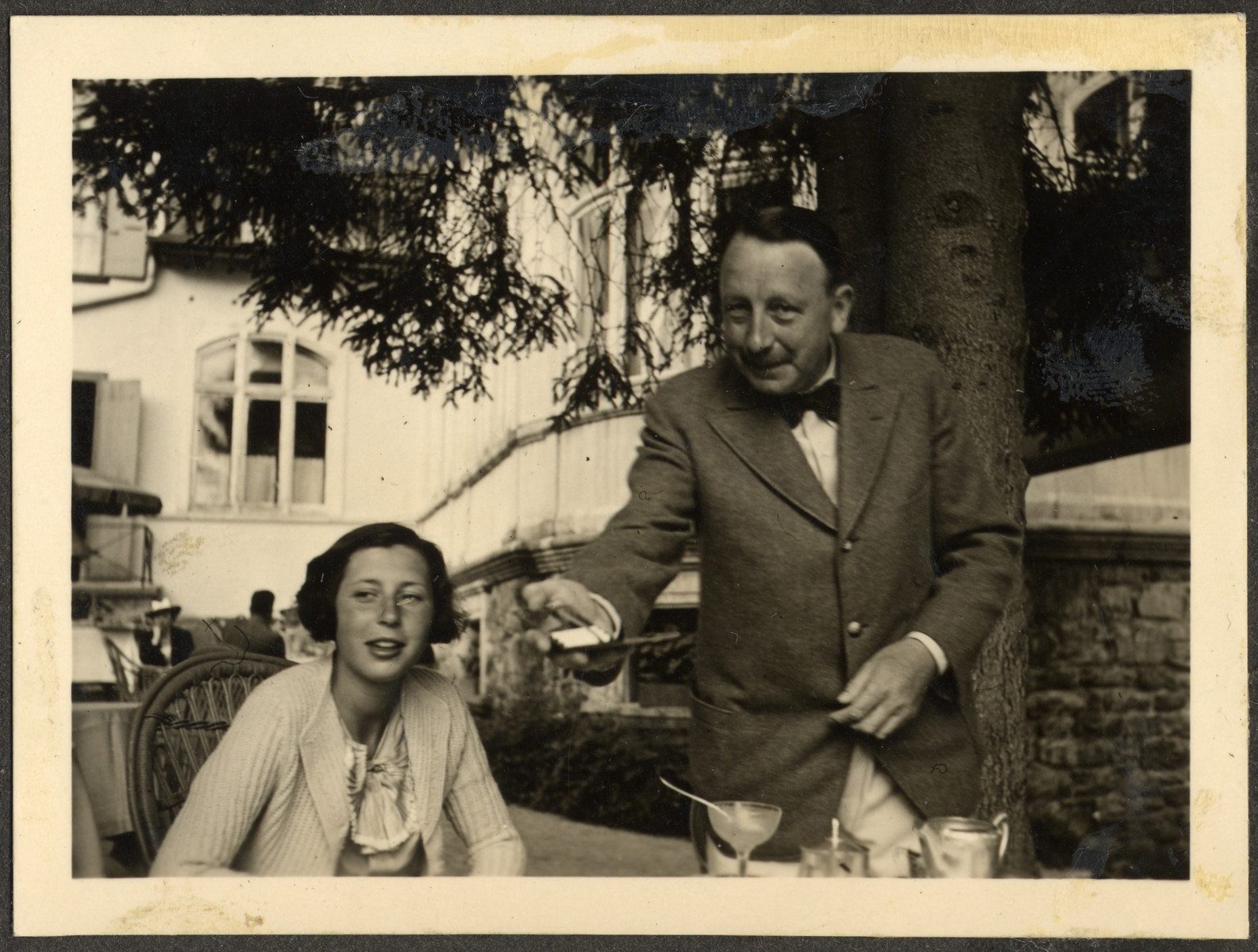 Annelise Bing and her father Ernest enjoy a snack on an outdoor terrace.