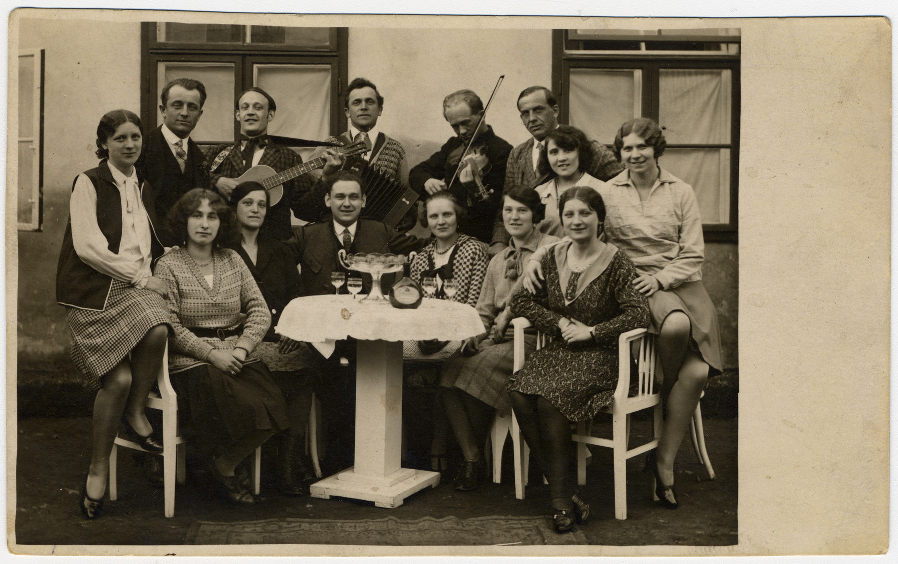 A group of friends gathers around a table, with musicians in back.  Among those pictured is Martha Holzmann (seated at  lower left).